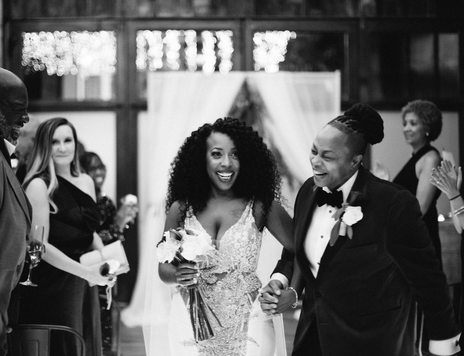 A newlywed black lesbian couple walks down the aisle smiling and laughing at Brooklyn Winery