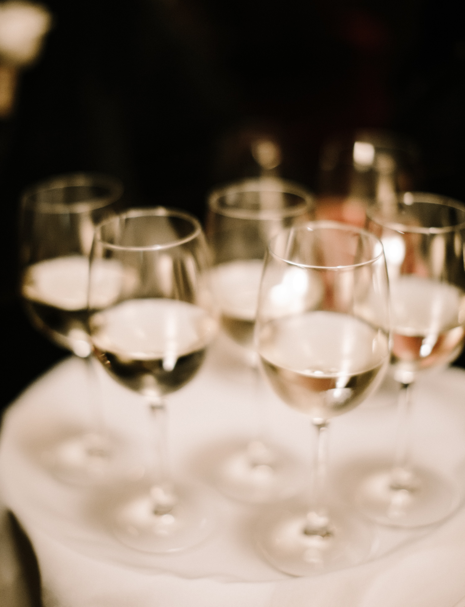 Soft glasses of white and rosé wine rest on a tray in the dark at Brooklyn Winery in New York City