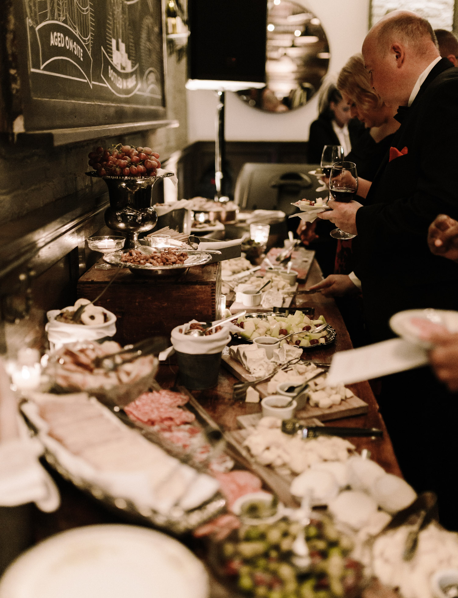 Guests line up to enjoy an abundant charcuterie spread at a Brooklyn Winery wedding reception in New York City