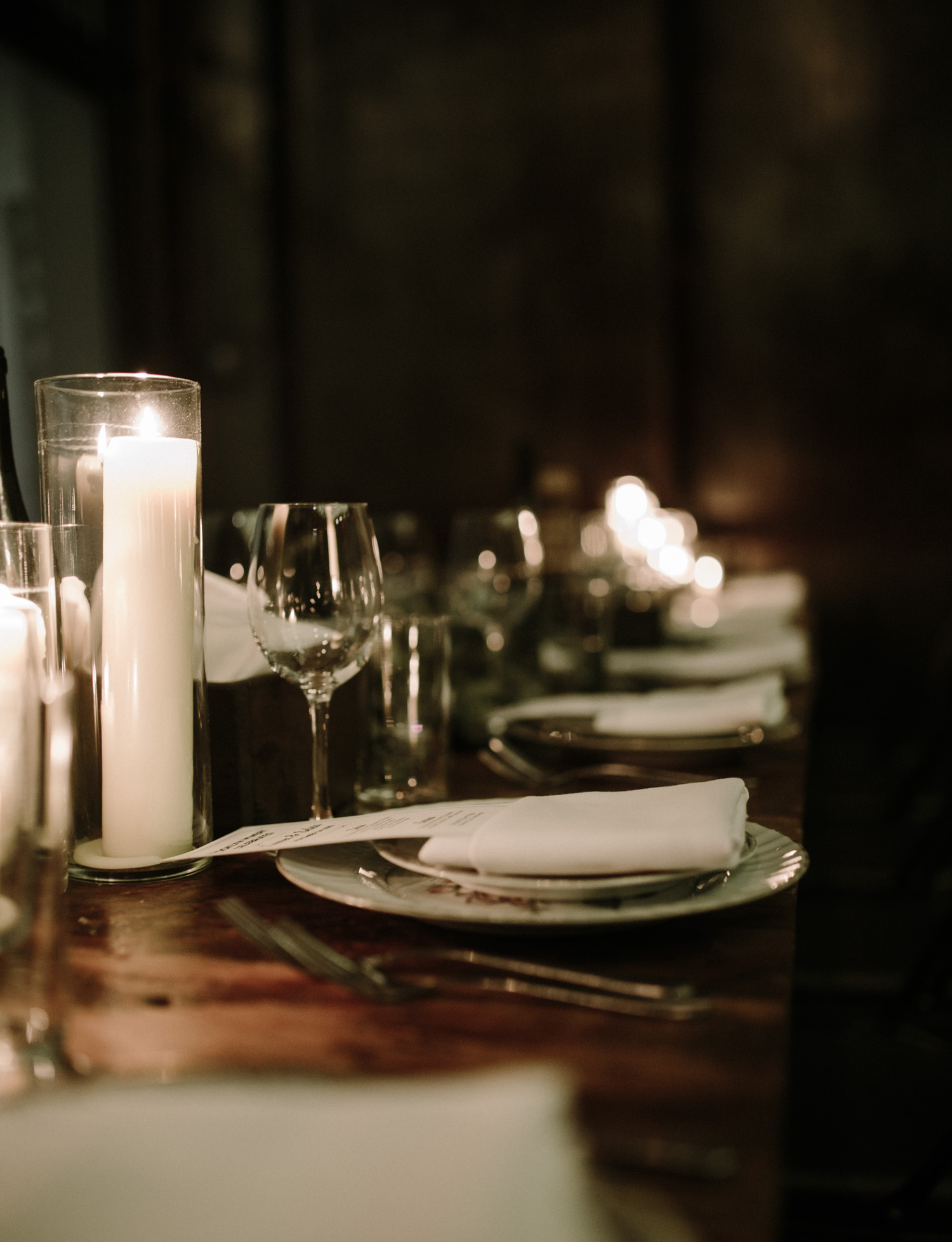 A wood wedding reception table at Brooklyn Winery in New York with candles, wine glasses, and greenery