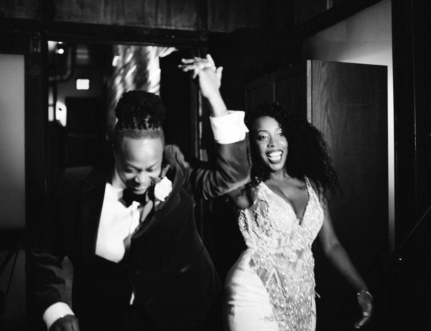 A smiling black same sex couple have their grand entrance to their winter wedding reception at Brooklyn Winery in New York City