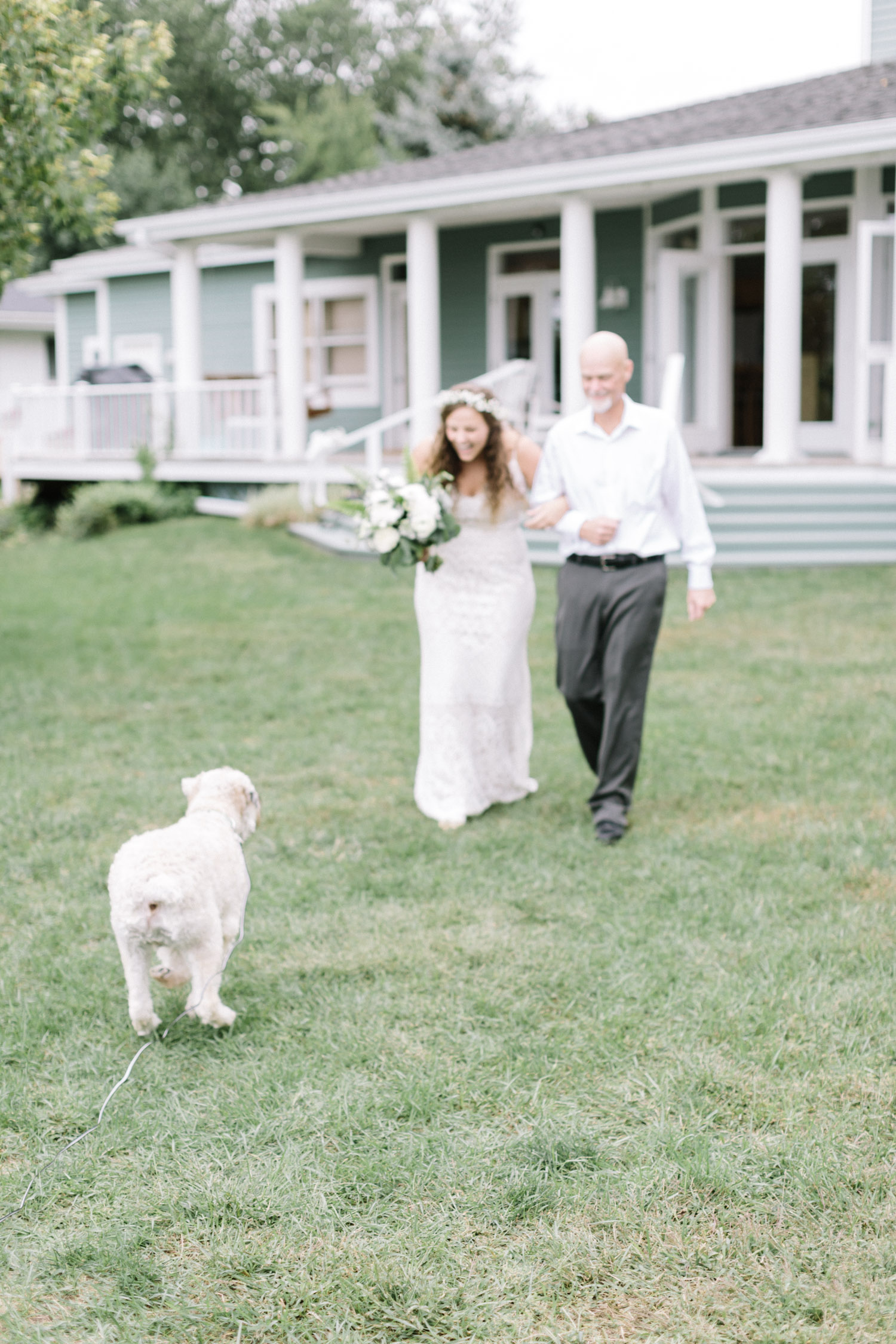 Motion blur is caught as the ring bearer dog breaks free and runs toward the bride & her father while they walk down the aisle at her Michigan wedding
