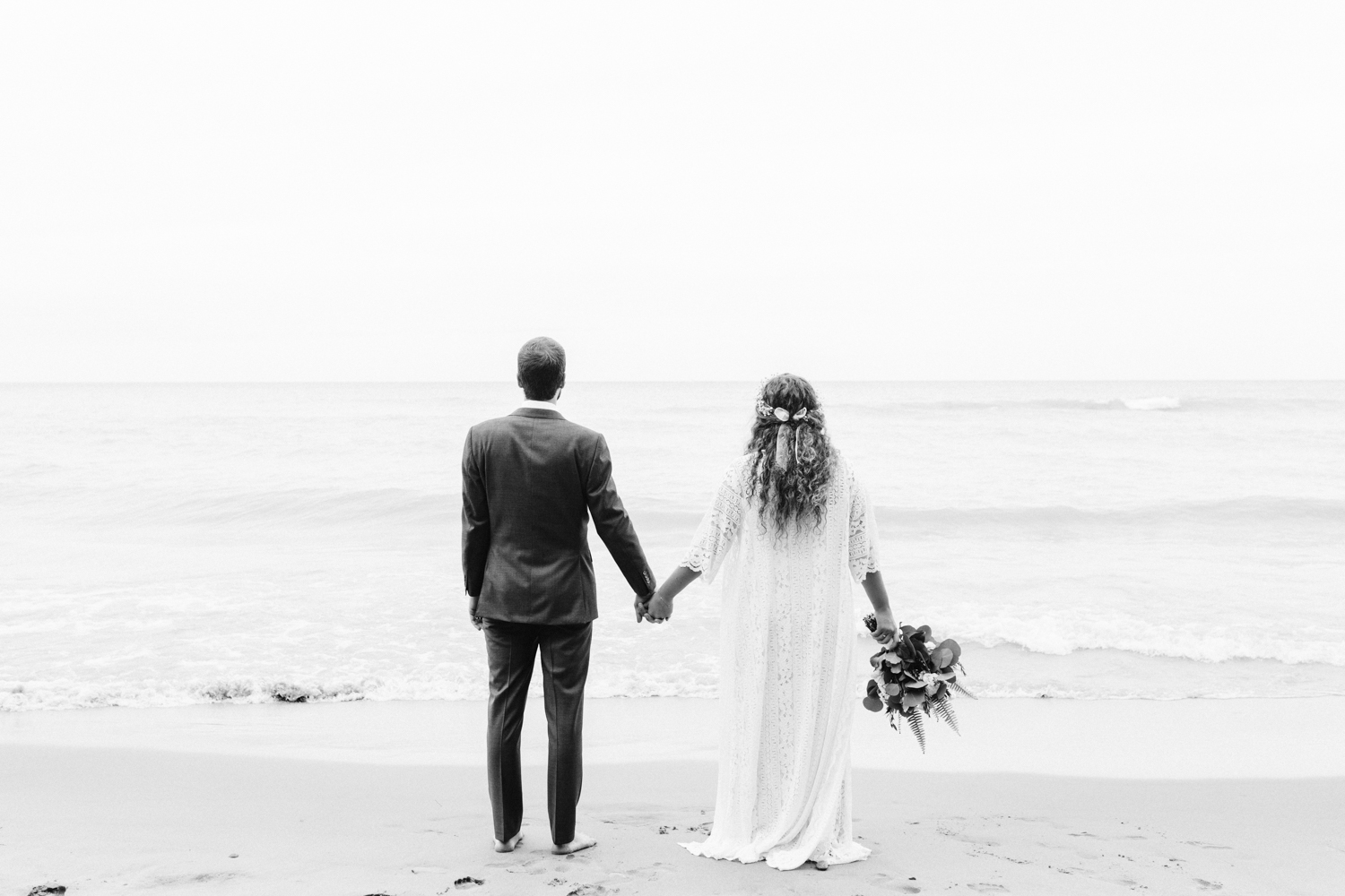 A bride and groom stand hand in hand, looking out at Lake Michigan on their September wedding day