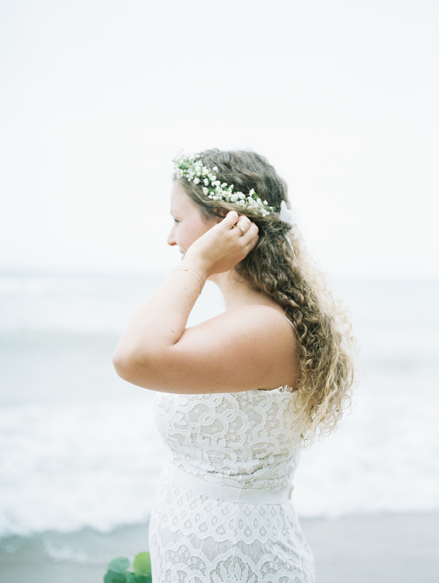 a curly haired bride in a boho flower crown pauses to gaze at Lake Michigan on her September wedding day