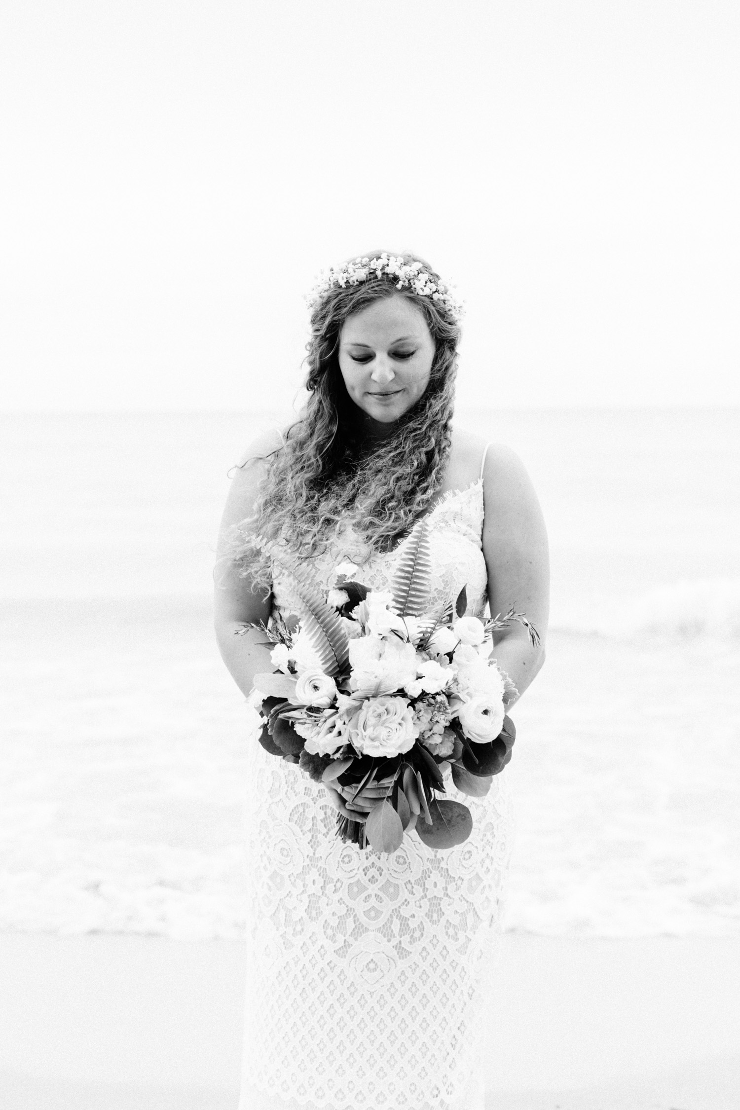 A boho curly haired bride with a flower crown and the wind in her hair on a Lake Michigan beach, just after her small wedding ceremony