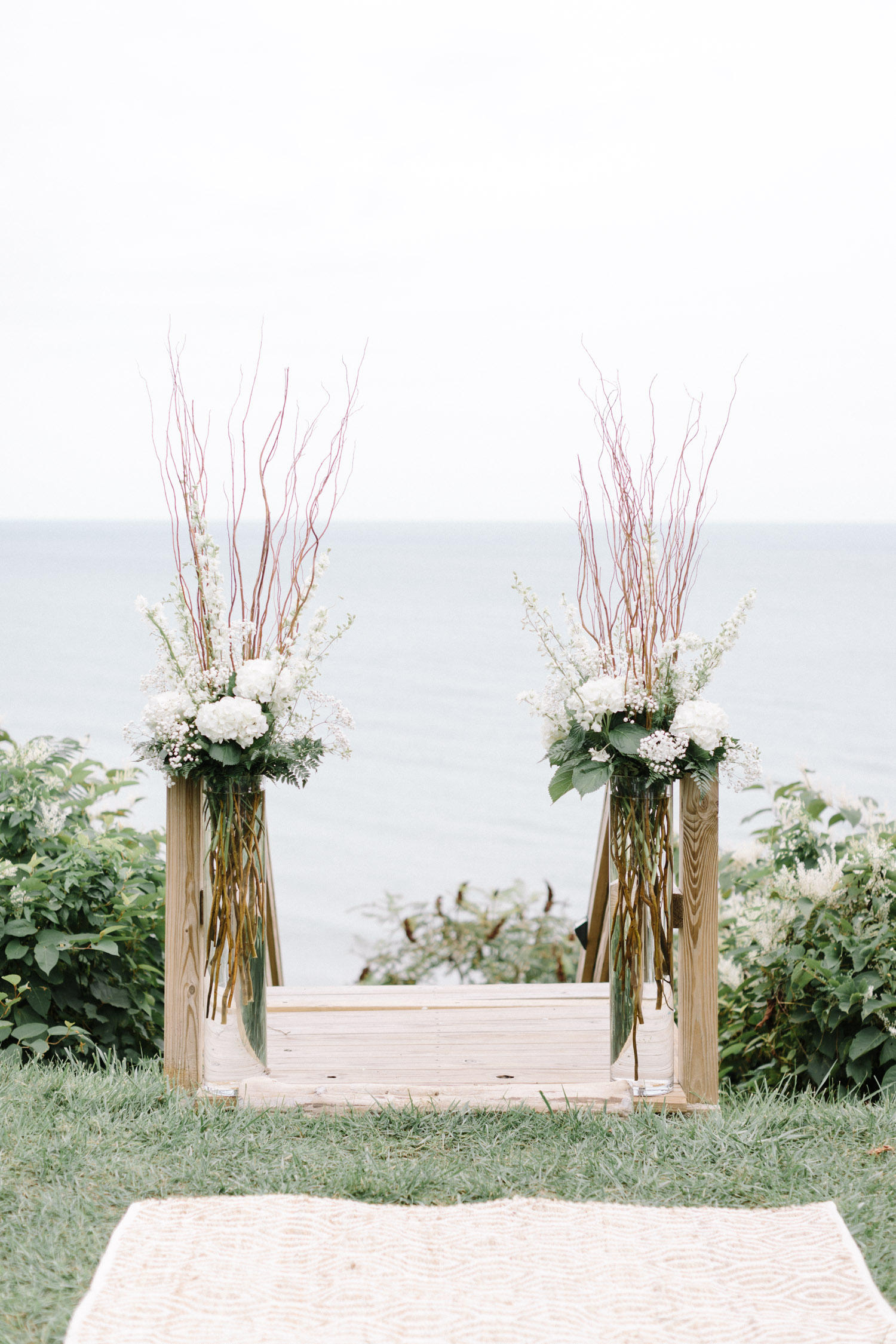 green and white floral arrangements with tall branches serve as wedding ceremony decor for a Lake Michigan September wedding