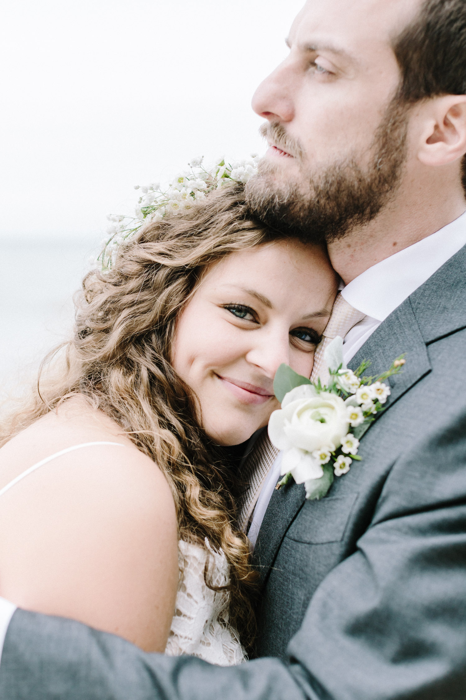 A curly haired bride smiles with her head on her groom's chest as they explore a Lake Michigan beach after their small West Michigan wedding ceremony
