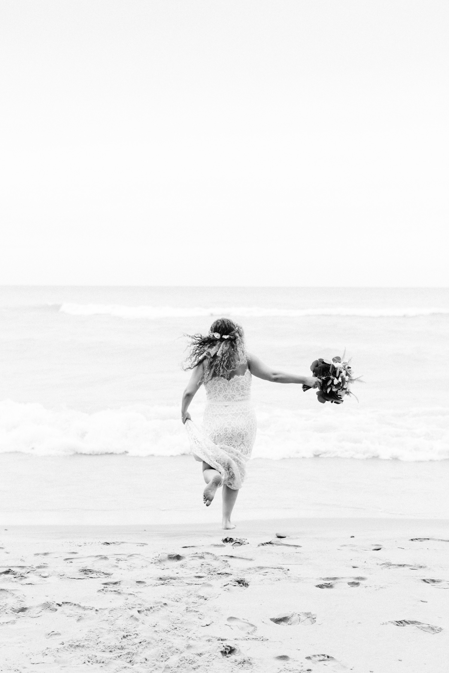 A curly haired bride in a relaxed lace BHLDN wedding dress runs freely into Lake Michigan