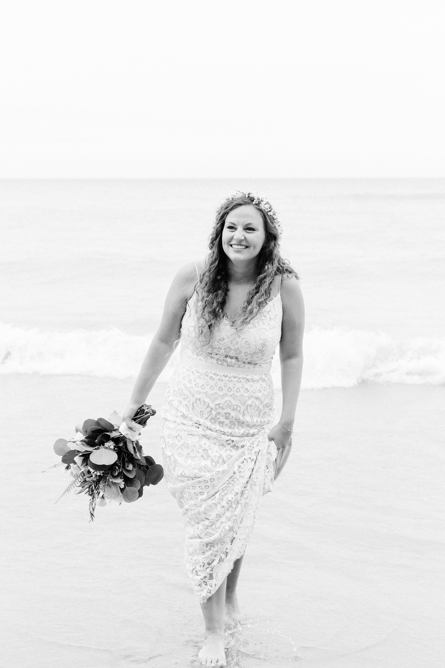 A boho bride in a relaxed lace BHLDN wedding dress laughs as she wets her feet in Lake Michigan
