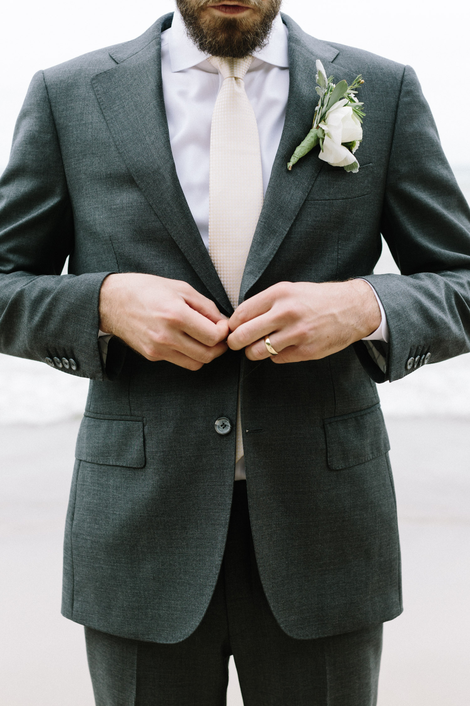 A groom's hands and gold wedding band are seen as he buttons up his grey suit jacket on a Lake Michigan beach