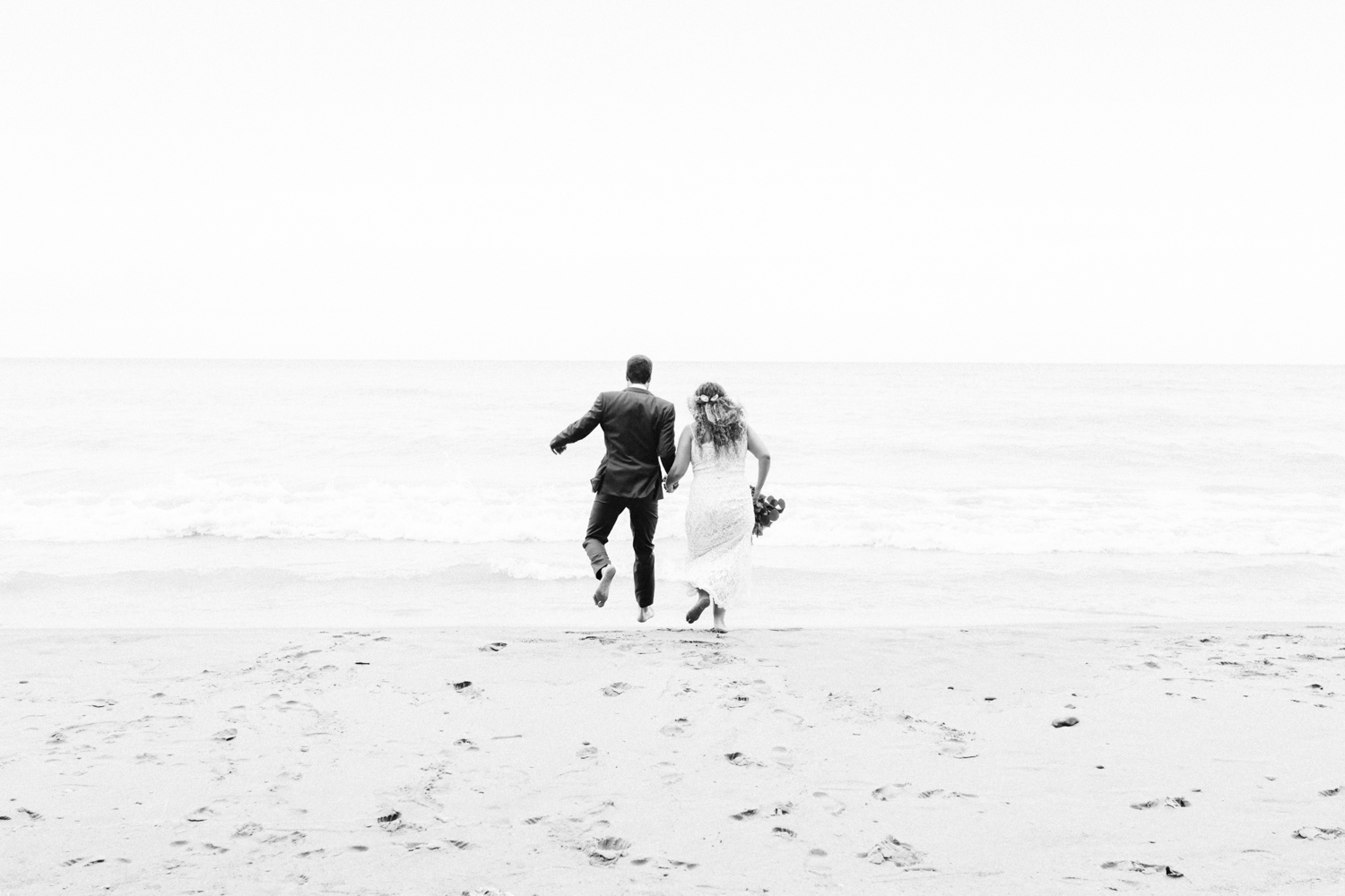 A bride and groom are seen from behind, running and jumping hand in hand into Lake Michigan