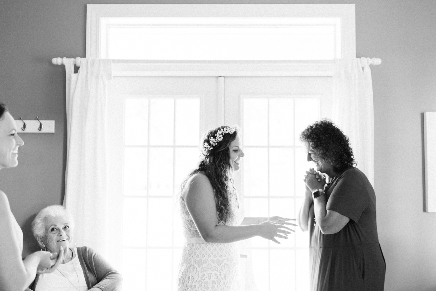 A bride reaches out for her mother, who beams with excitement as she prepares for her Lake Michigan wedding