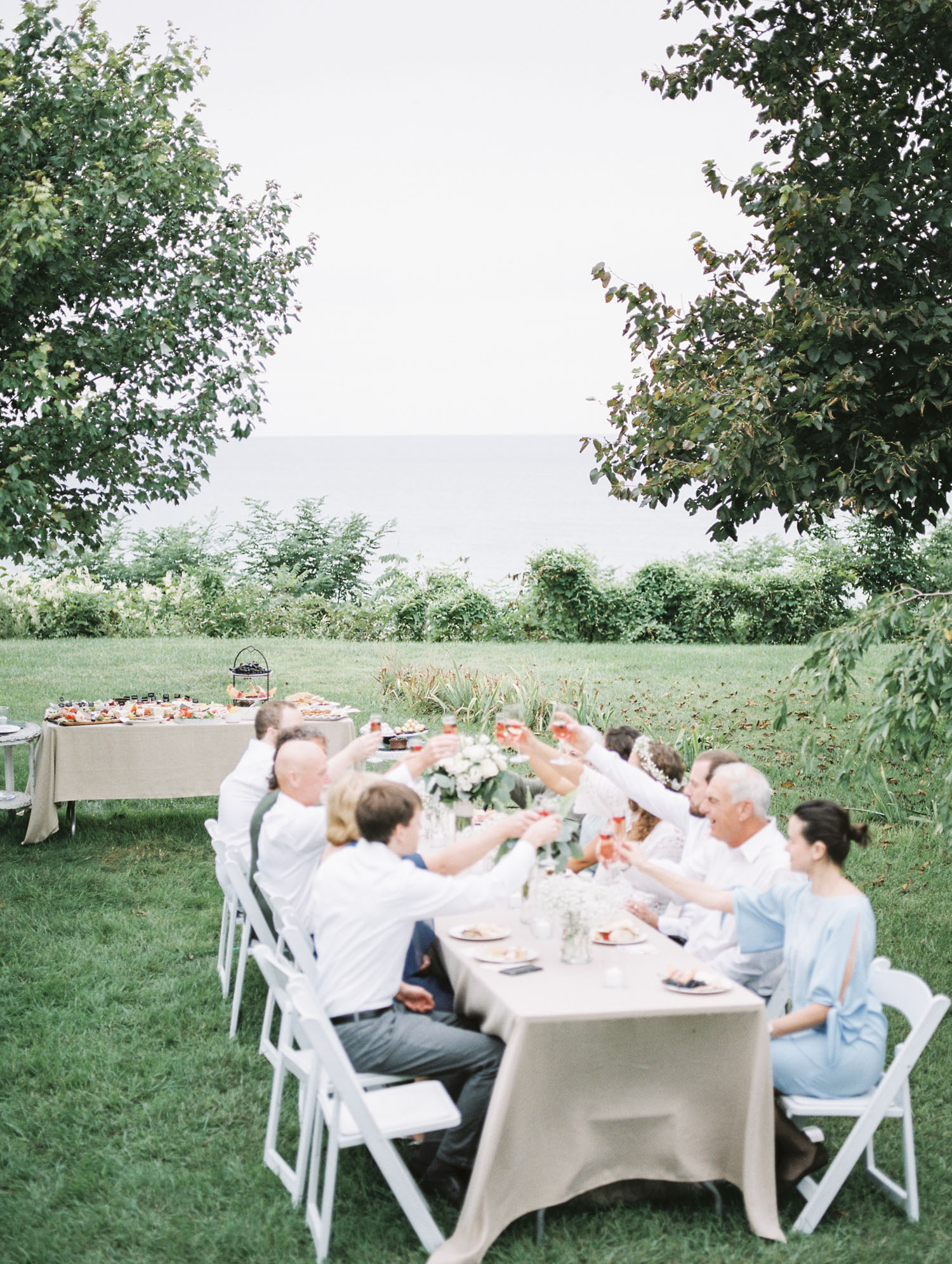Wedding guests toast their glasses at a shared table overlooking Lake Michigan