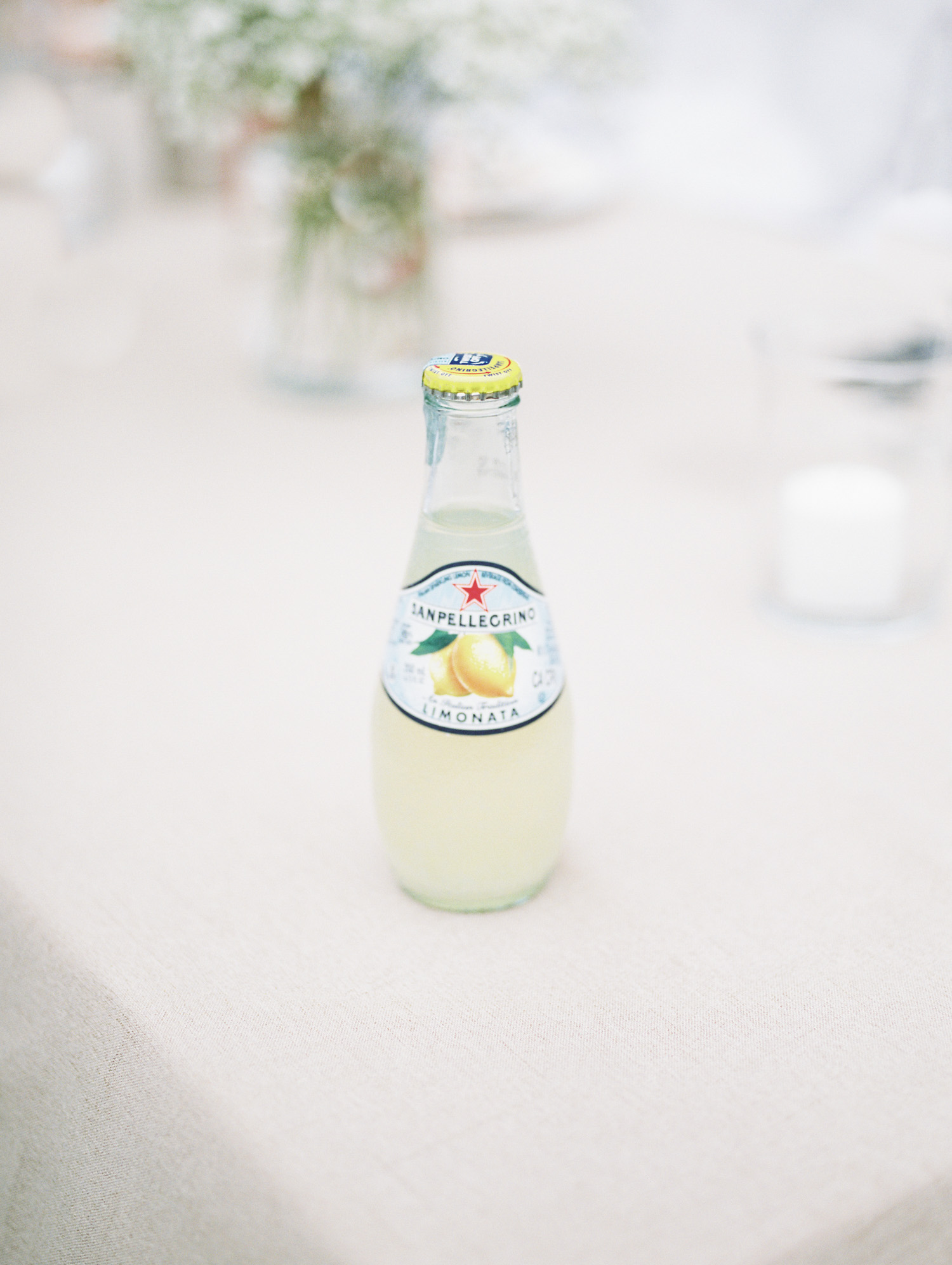 A bottle of san pellegrino sits on a table at a small Lake Michigan wedding celebration