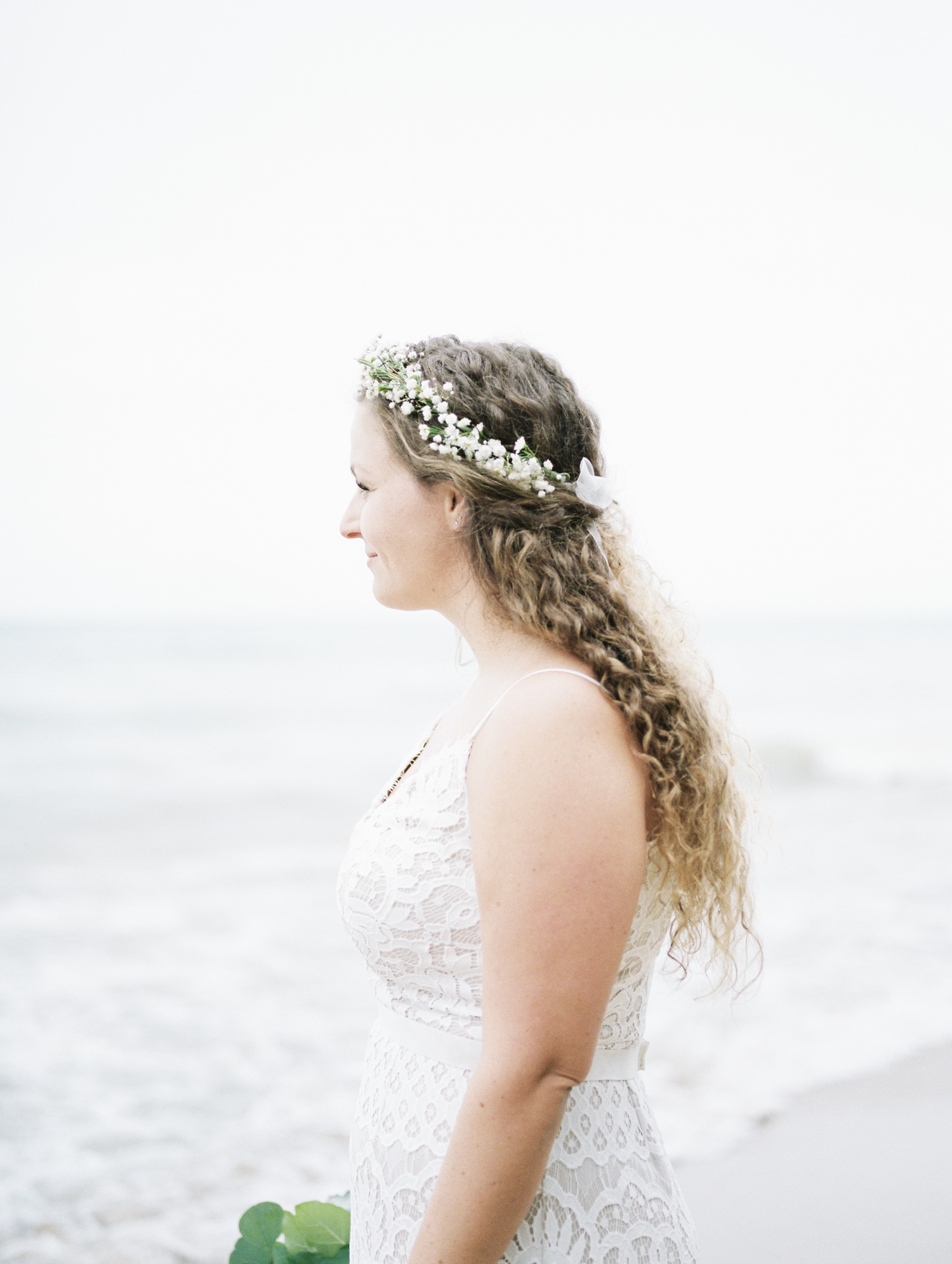 A curly haired bride with relaxed boho style and a delicate flower crown looks out at Lake Michigan from a west Michigan beach after her small wedding