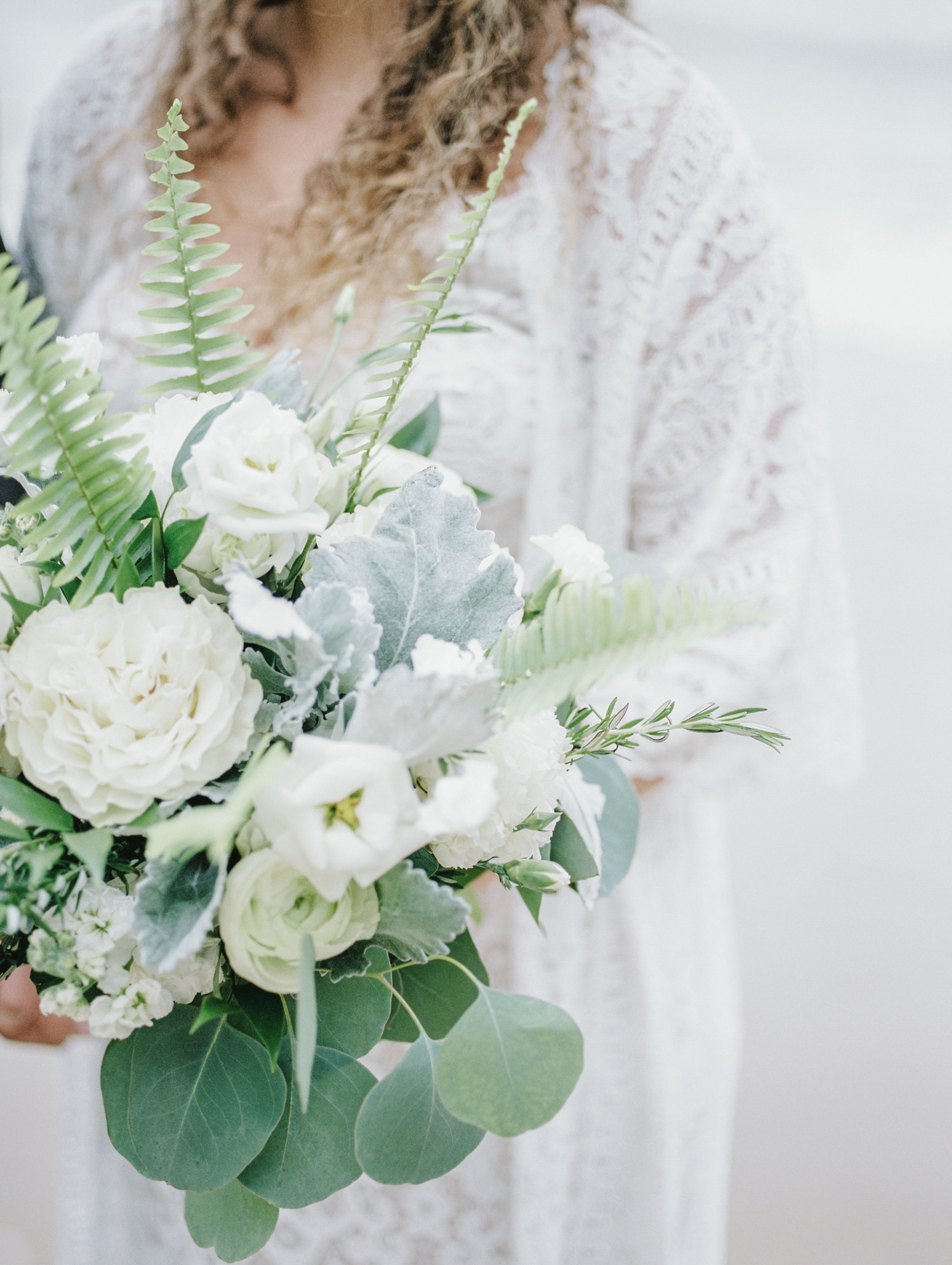 A wedding flower bouquet with white lisianthus, greenery, and ferns at a Lake Michigan wedding