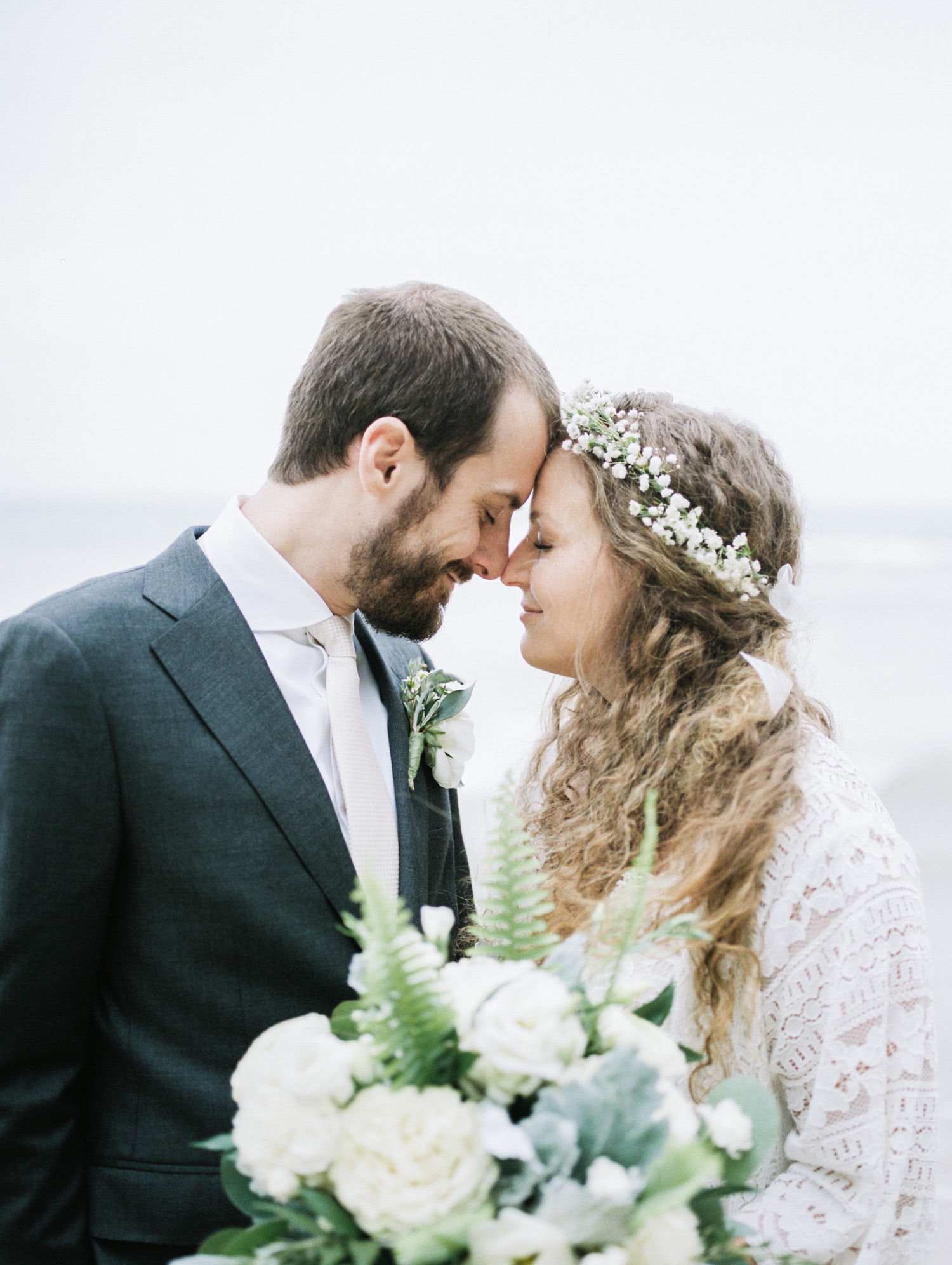 A curly haired bride and her groom share a quiet moment connecting on a Lake Michigan beach after their intimate West Michigan wedding ceremony