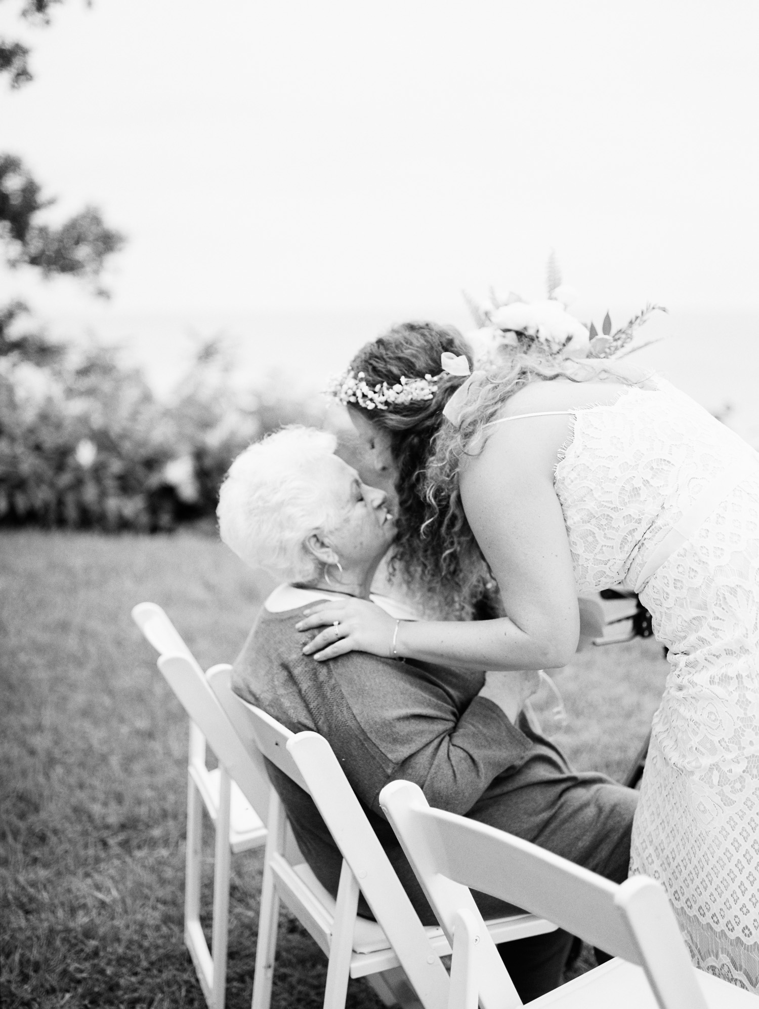A bride leans in to kiss her grandmother at her wedding overlooking Lake Michigan