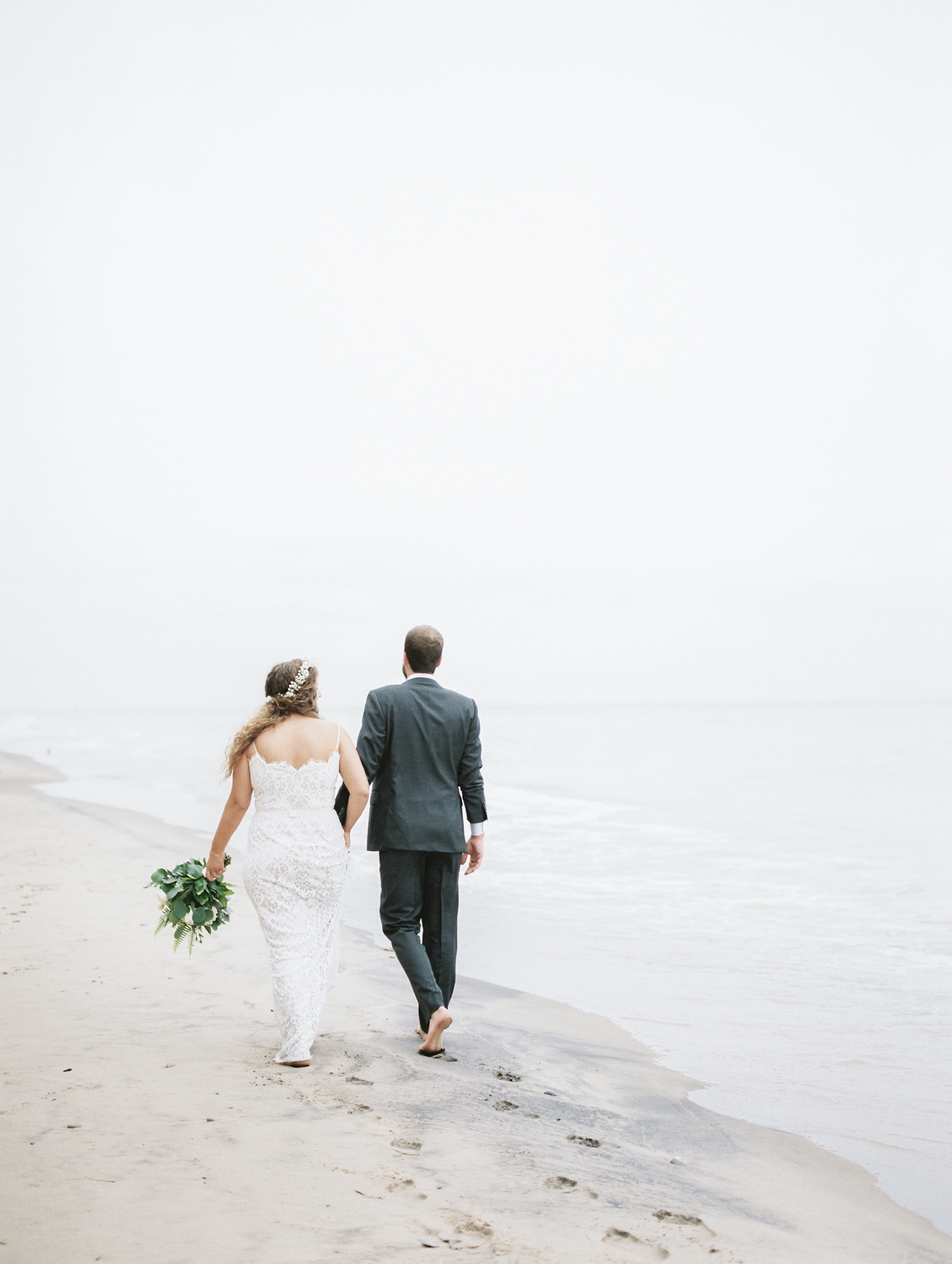 A bride and groom walk together down a Lake Michigan beach just after their small, intimate September wedding in west Michigan