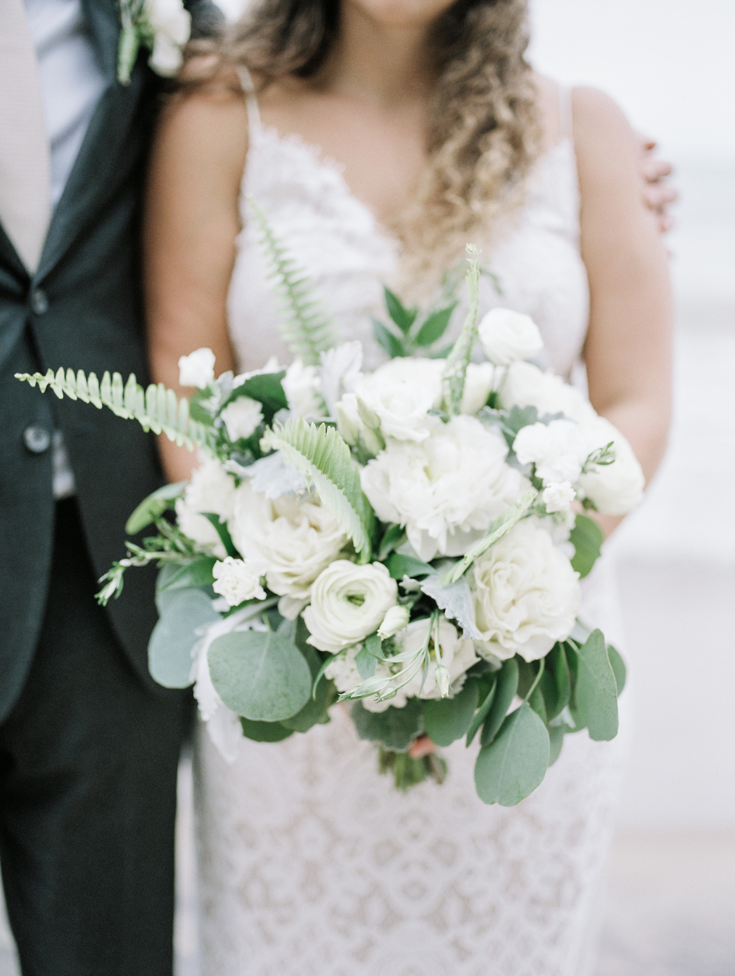 An organic wedding bouquet of white and green with ferns, held by a bride at her Lake Michigan wedding