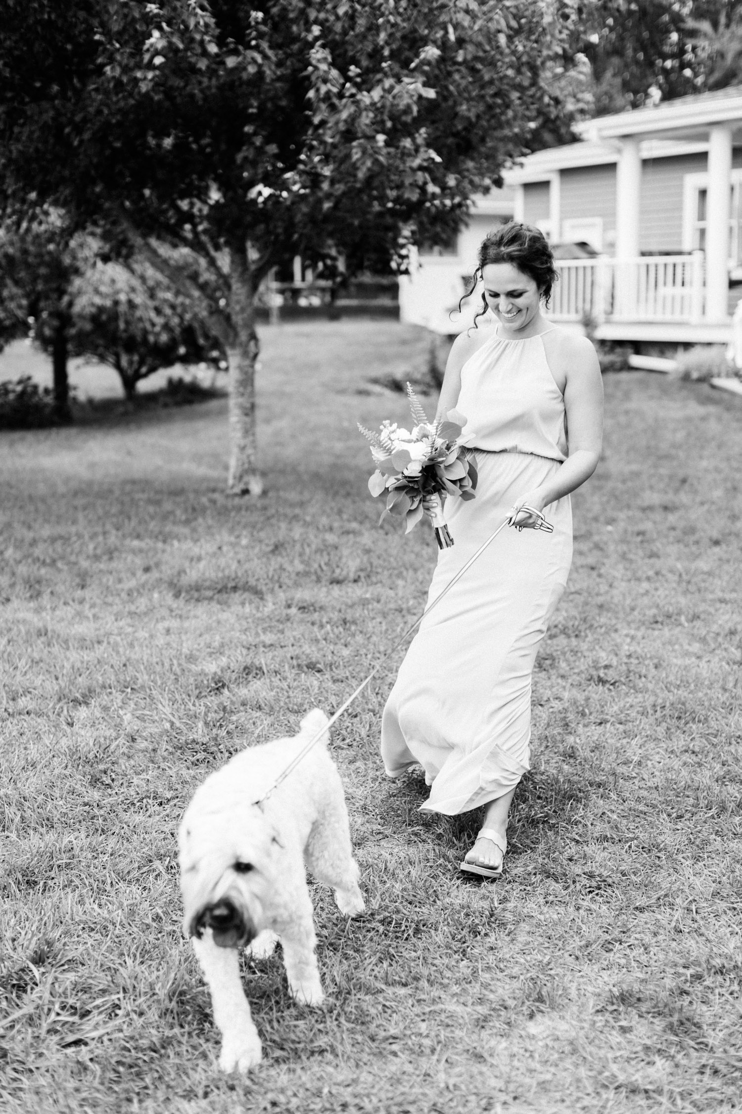 A bridesmaid walks a ring bearer dog down the aisle, laughing as he pulls her along