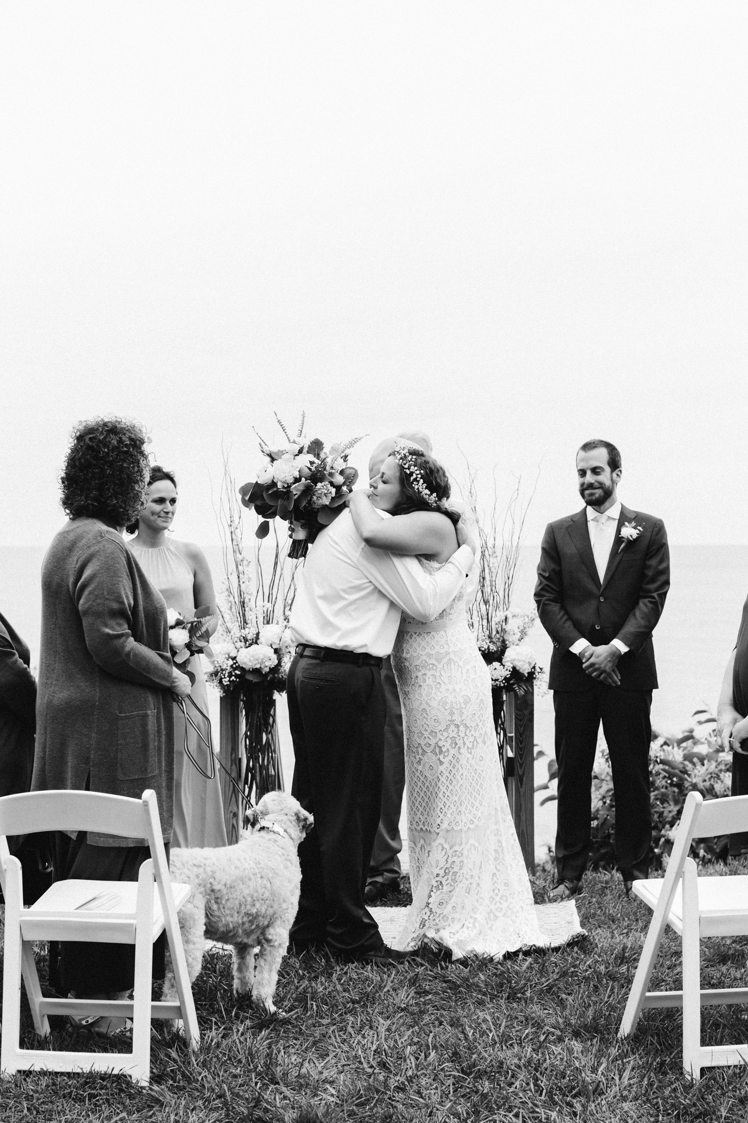 A bride & her father hug after walking down the aisle at her wedding overlooking Lake Michigan