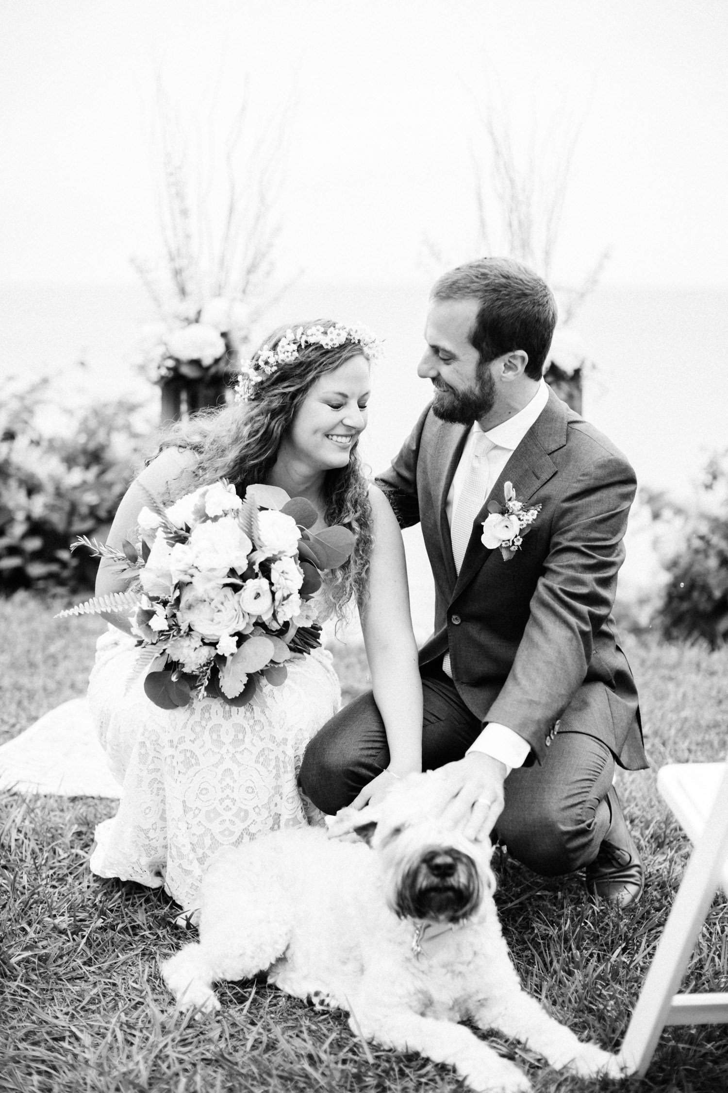 A joyful, candid moment is caught as a newlywed couple pause for a photo with their dog
