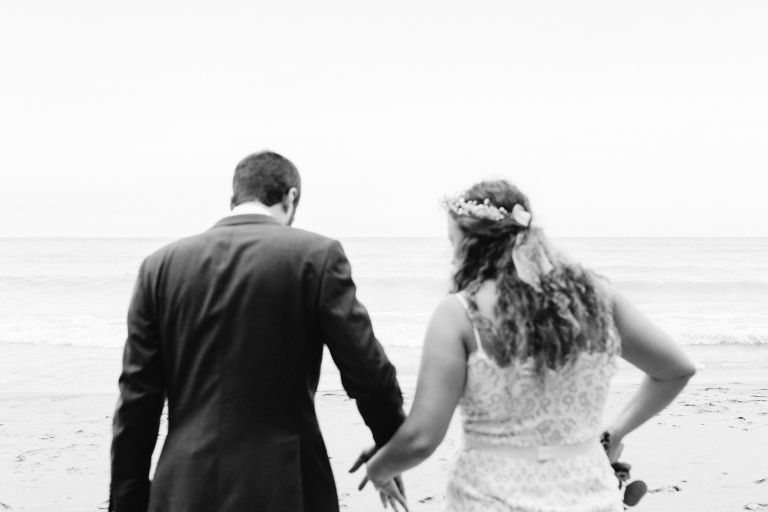 A bride and groom in the foreground begin to hold hands, Lake Michigan in focus in front of them