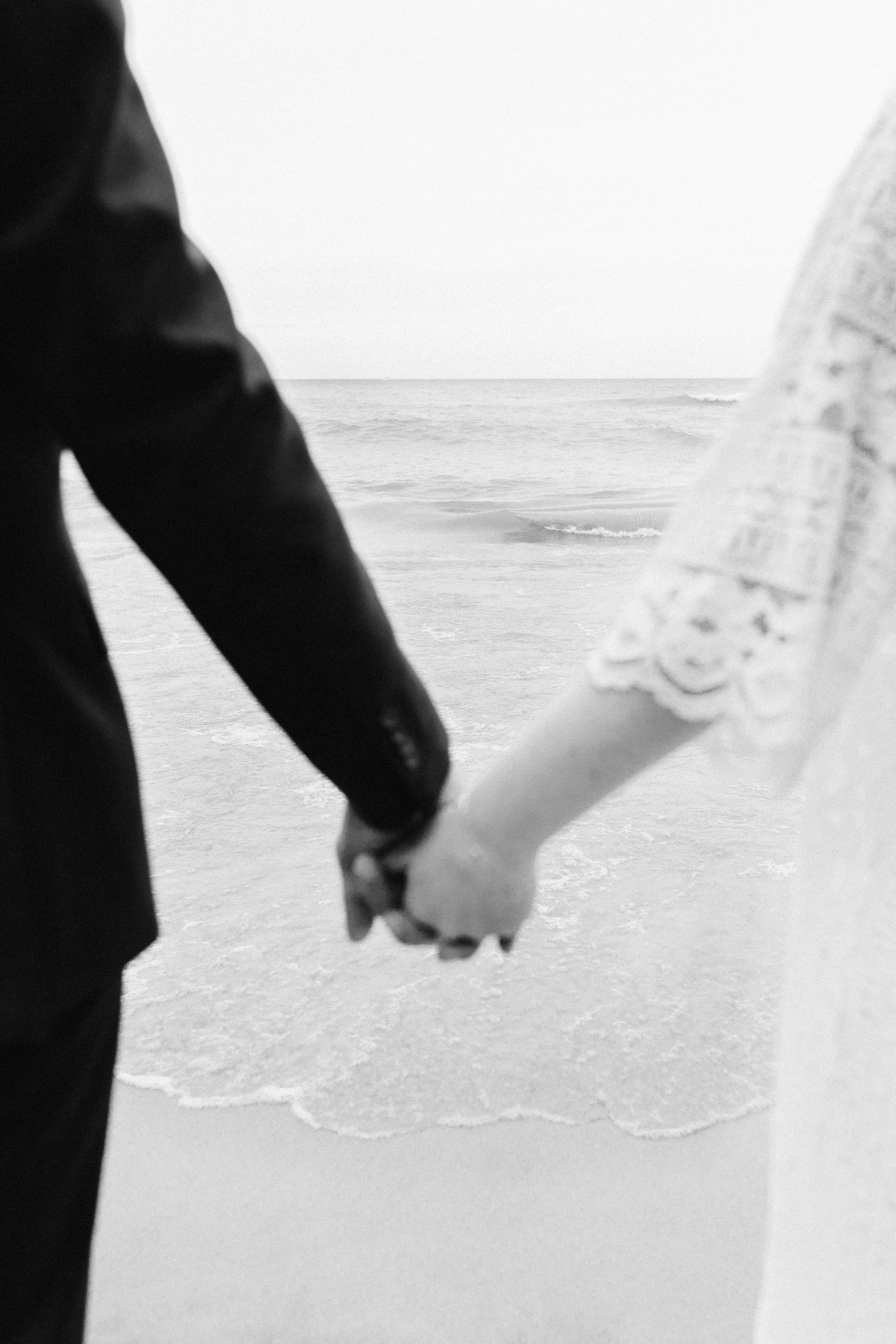 A bride and groom holding hands in front of the waves on a Lake Michigan beach, after their small wedding ceremony