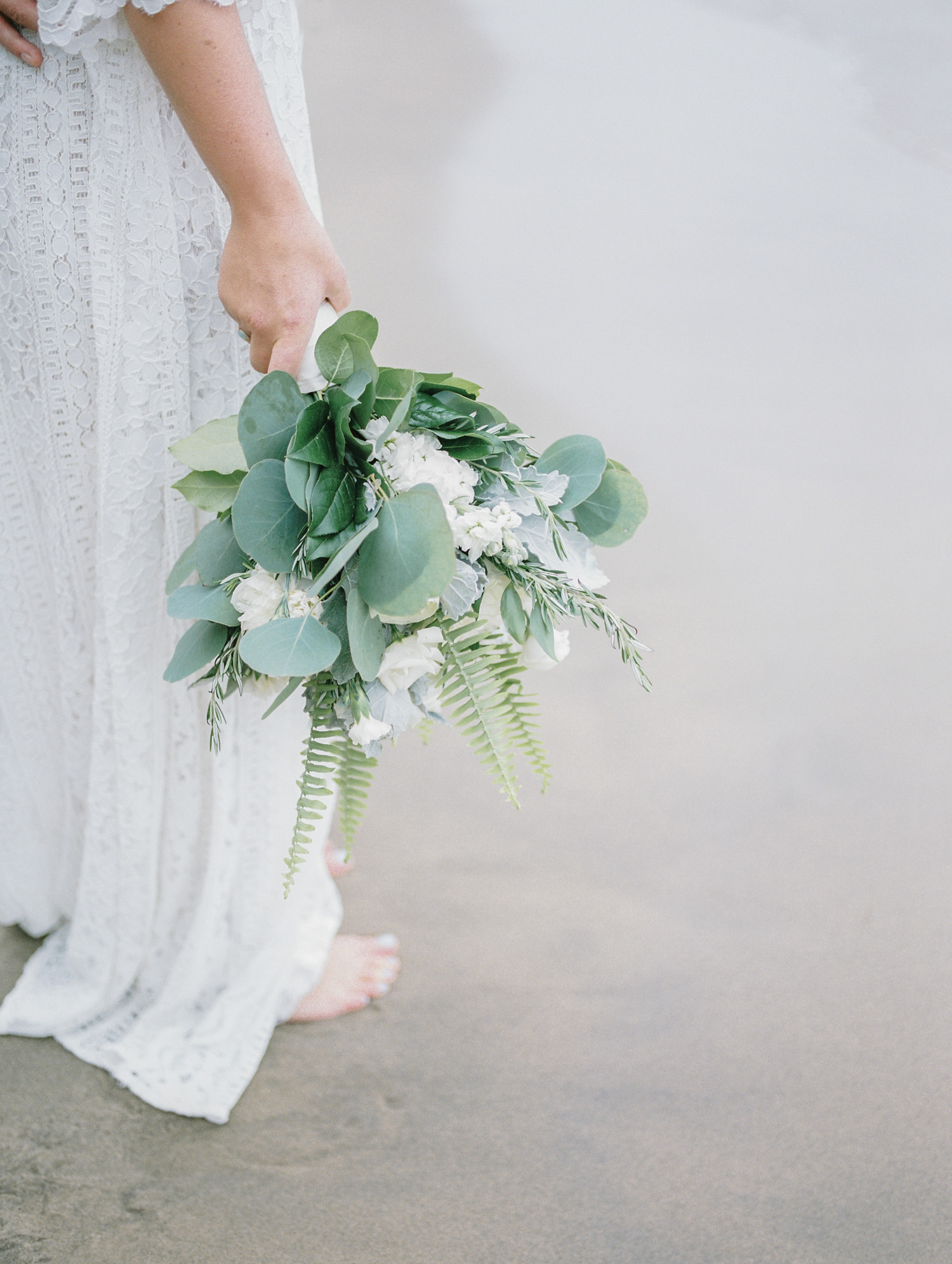 A bridal bouquet of eucalyptus, fern, and white flowers is held by a boho bride on a Lake Michigan beach