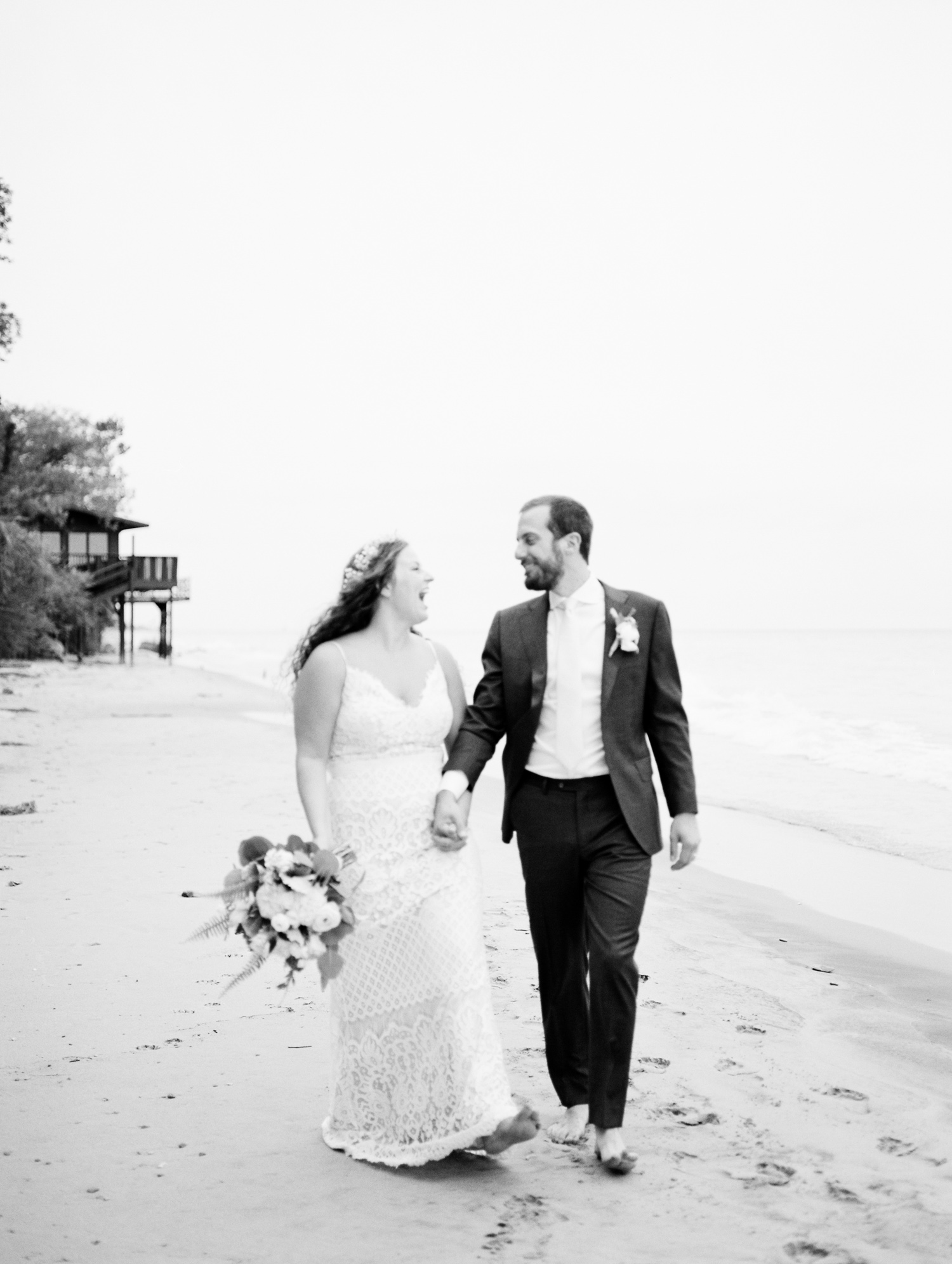A bride and groom hold hands and laugh while walking down a Lake Michigan beach, just after their West Michigan wedding