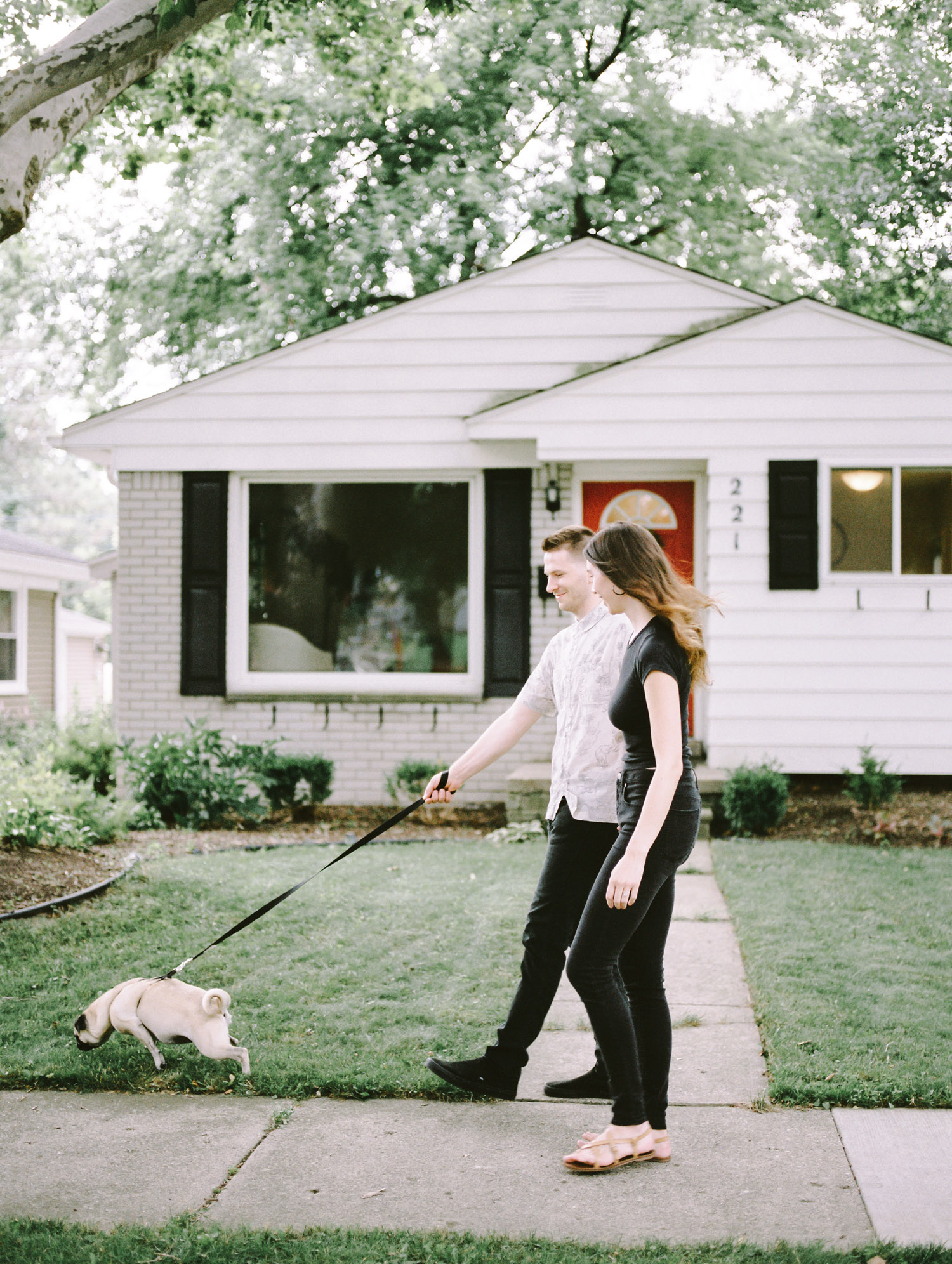 A young couple walks their dog during their at home photo session in Detroit, Michigan