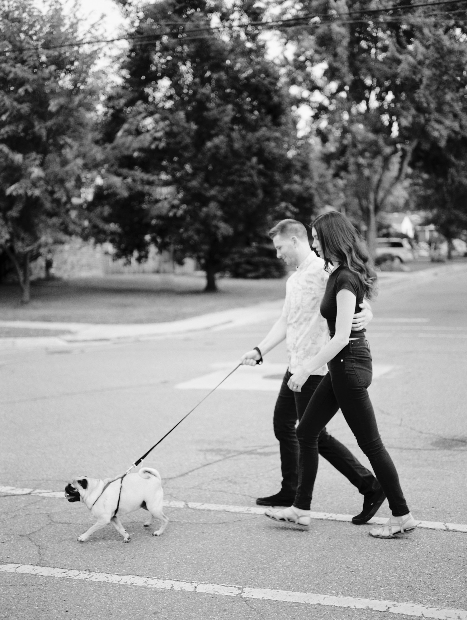 A young, stylish couple walks their dog for couple photos in Detroit, Michigan
