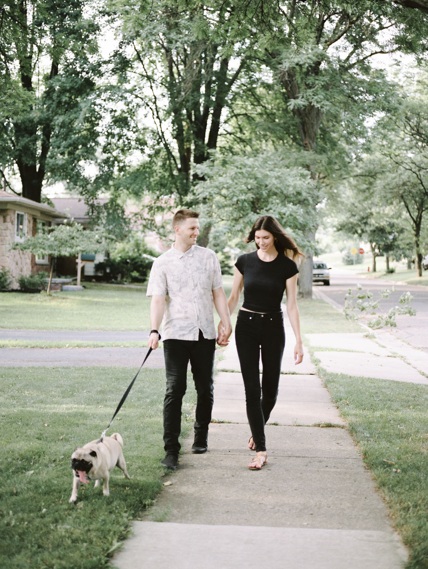 A couple holds hands while walking their pug in their Rochester, Michigan neighborhood for their Detroit couple photos