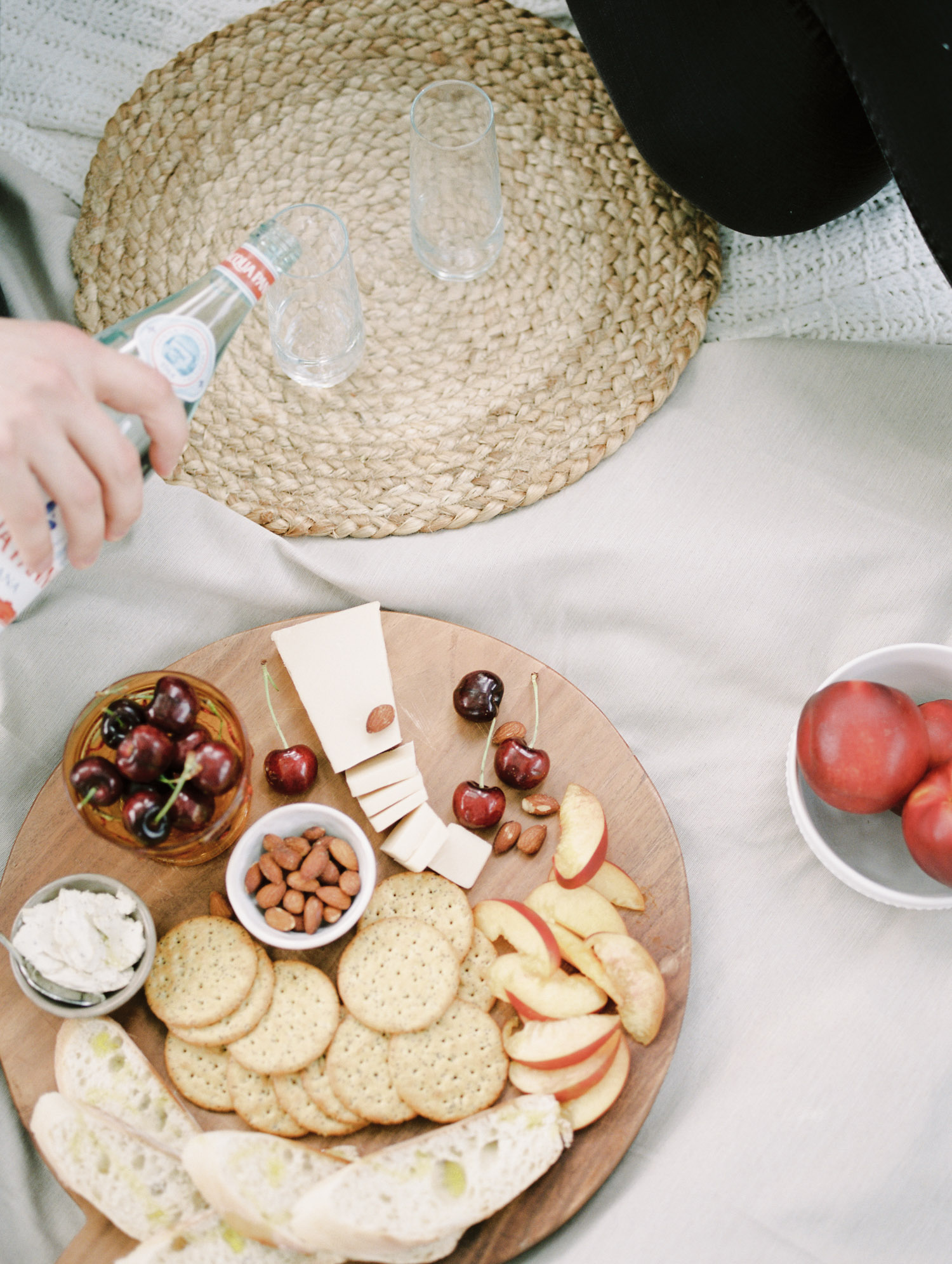A vegan charcuterie spread with cherries, almonds, and seasonal summer fruit during an at home session for a Detroit couple