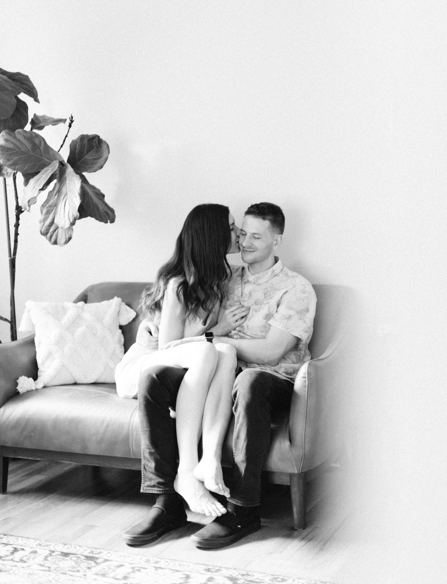 A Detroit couple cuddles on their couch in Rochester, Michigan during their at home photo session