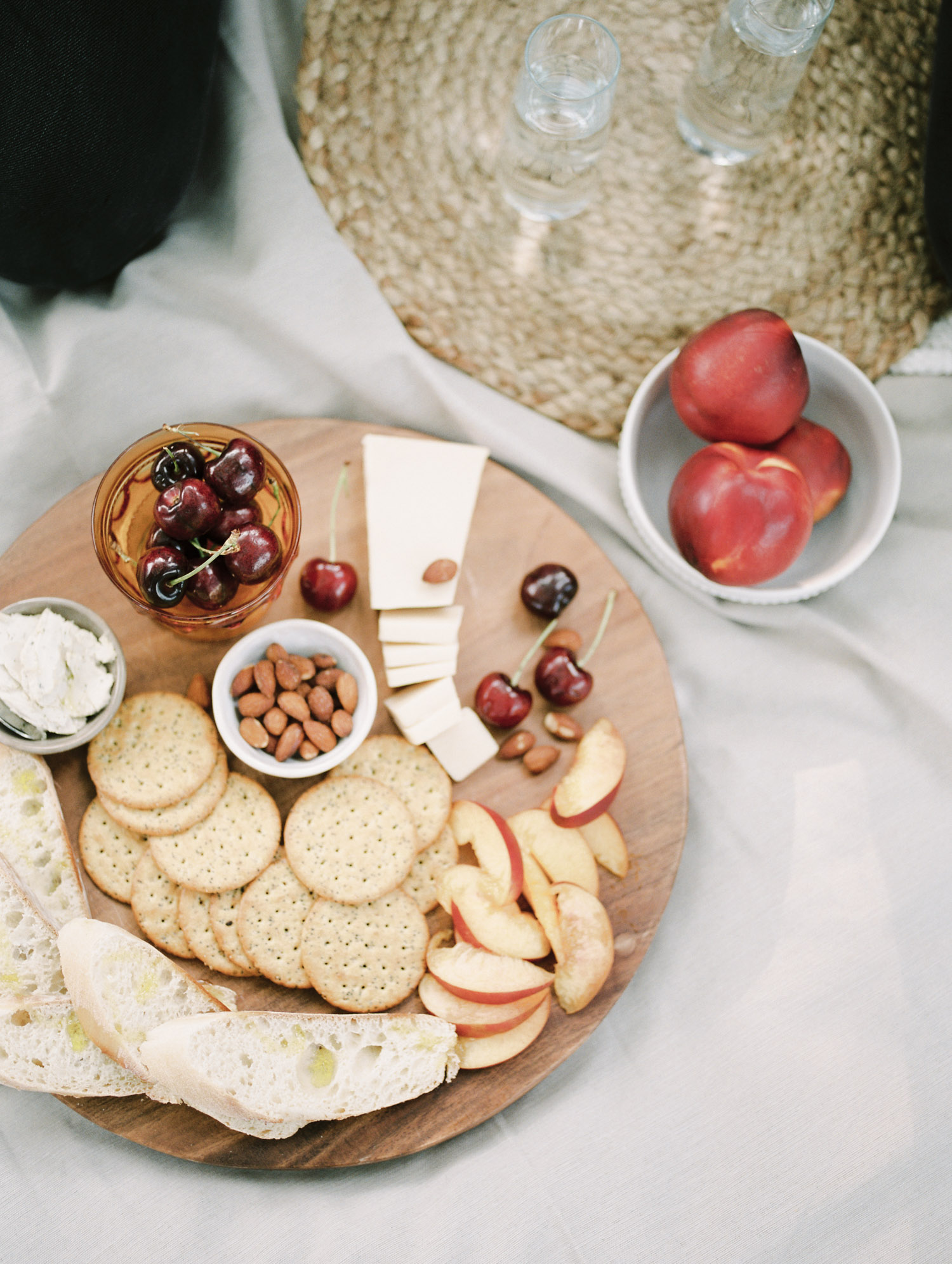 A vegan charcuterie spread on a wood board with vegan cheese, crackers, and seasonal fruit in Detroit, Michigan