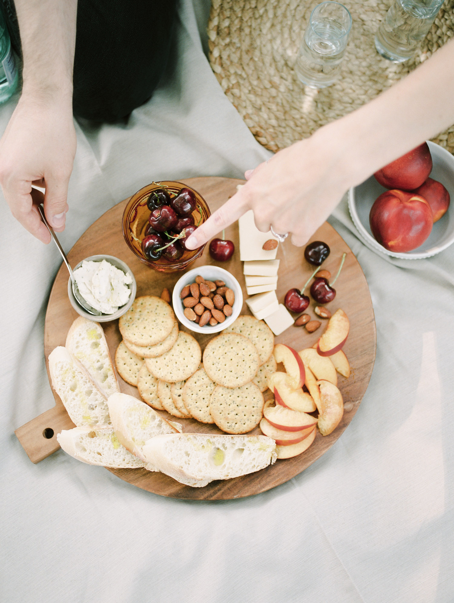 A bird's-eye view of a vegan charcuterie spread shows a woman's hand pointing at a vegan cheese in Detroit, Michigan