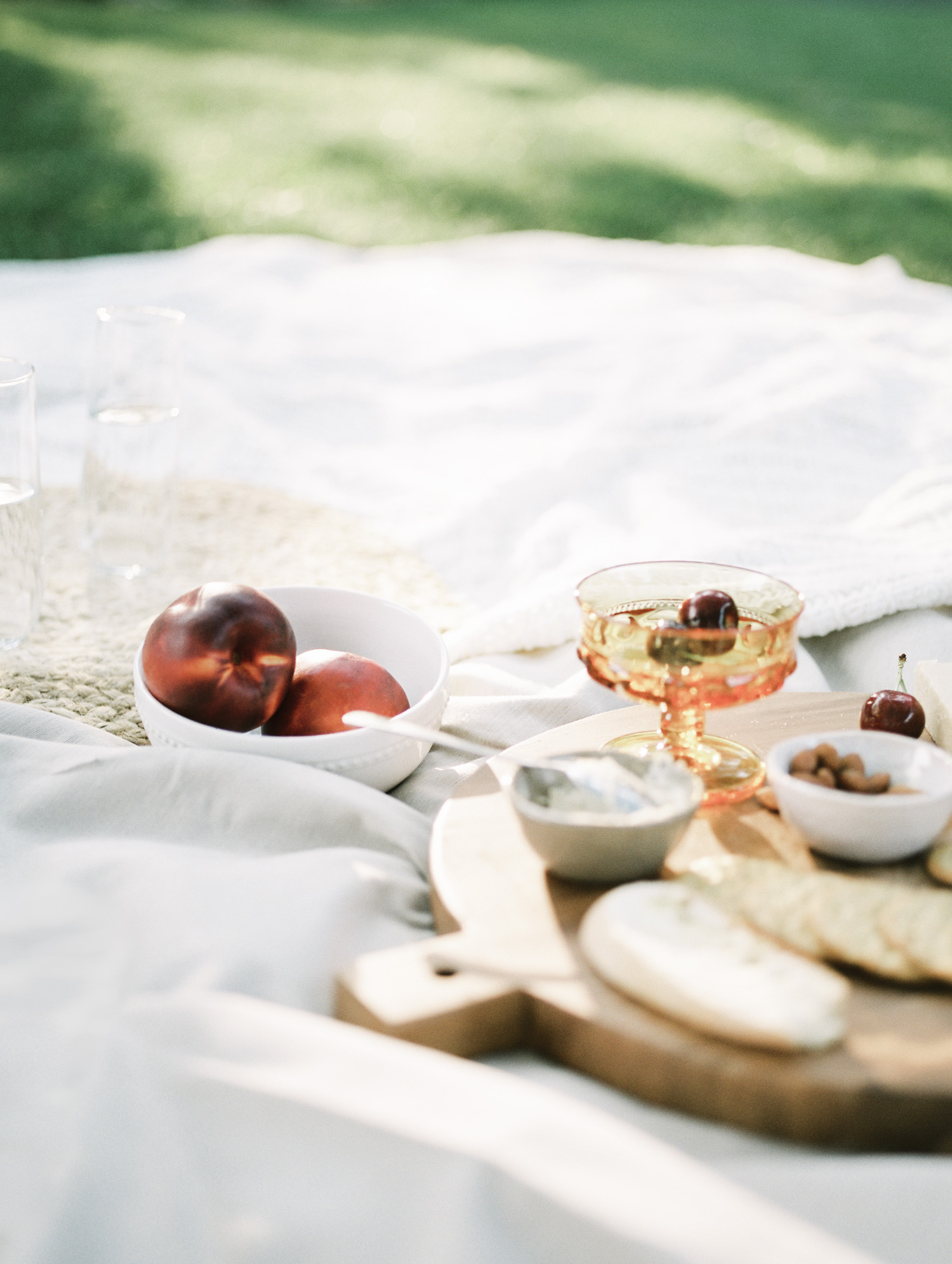 Peaches, cherries, and remnants of a vegan charcuterie spread rest on a picnic blanket after a Detroit couple's at home photos