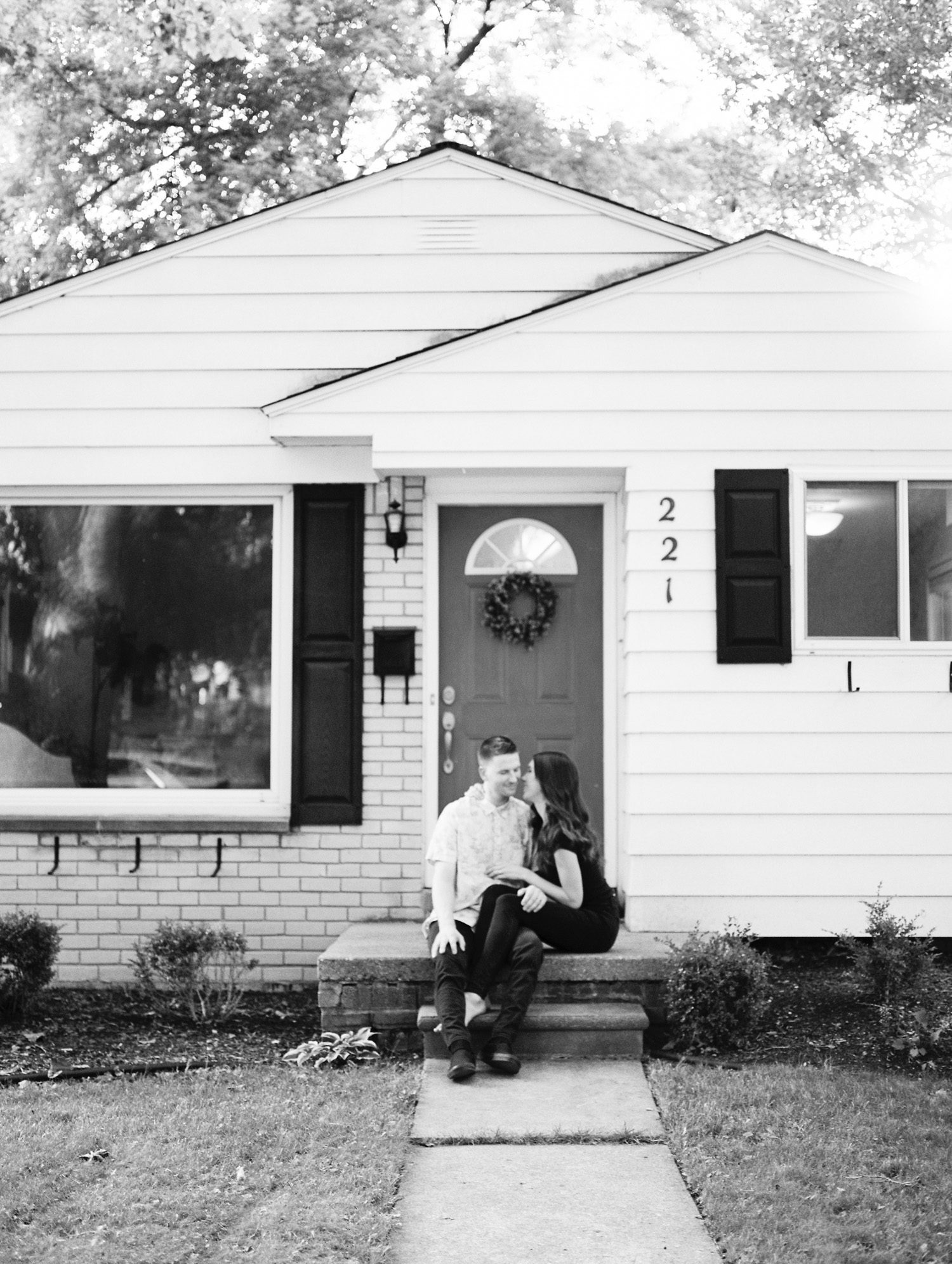A couple embraces on the porch of their Rochester, Michigan home during their at home photos near Detroit