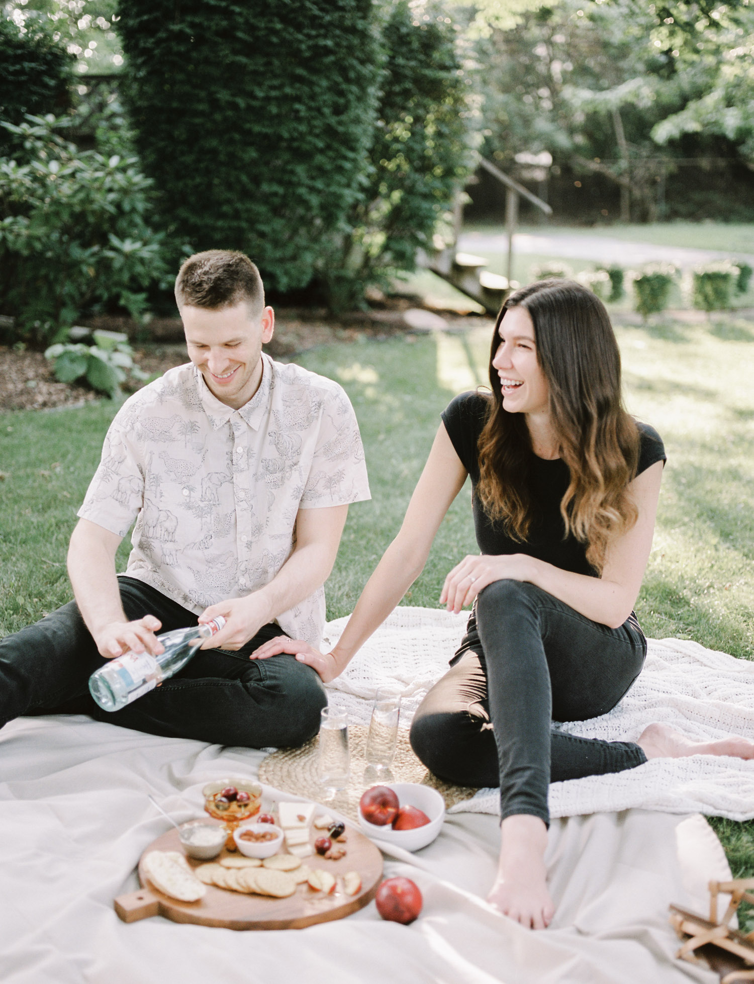 A couple laughs while having a charcuterie picnic during their Detroit at home couple photos