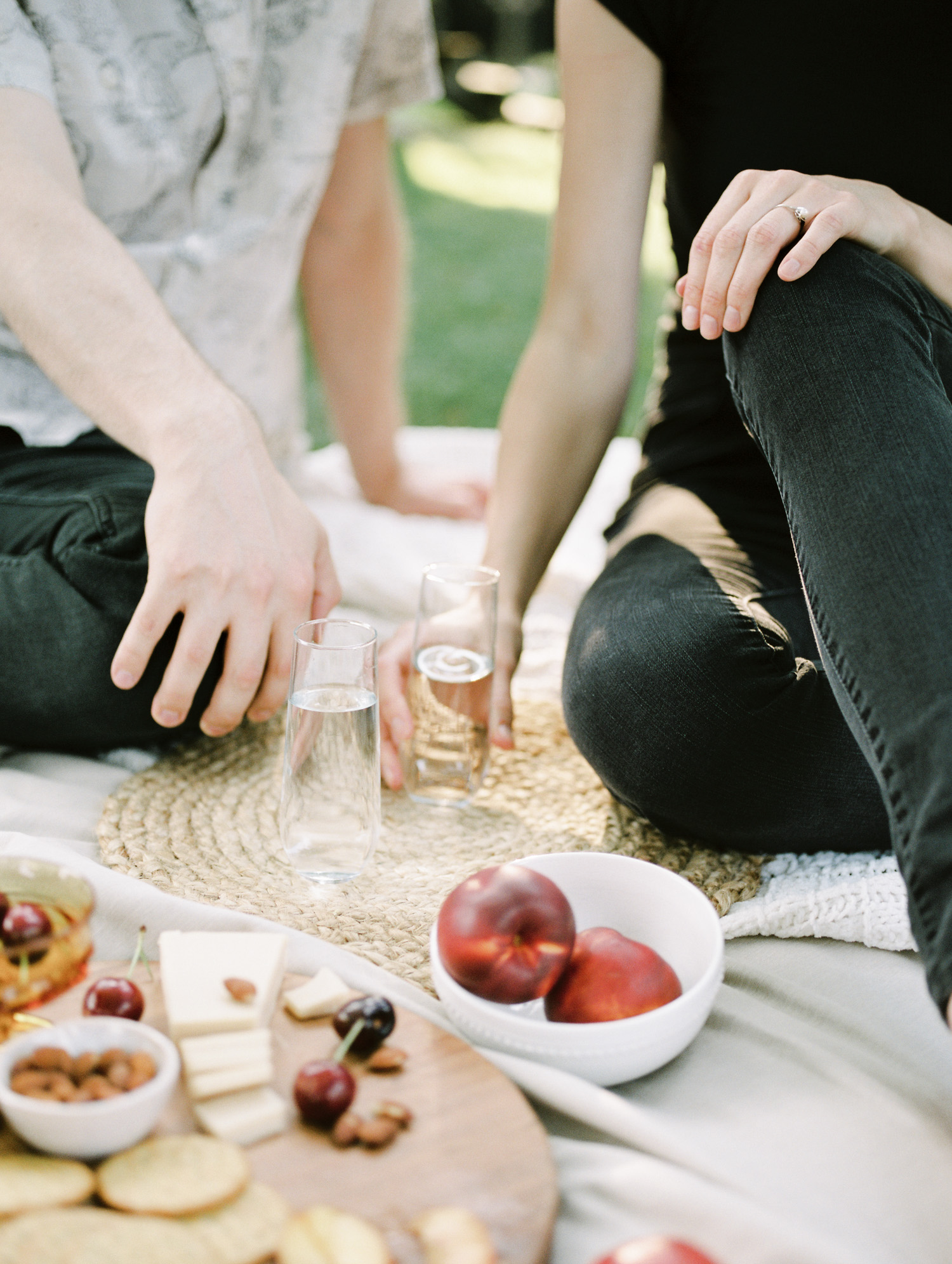 A couple's hands reach for their drinks during a vegan charcuterie picnic at their Detroit at home photo session