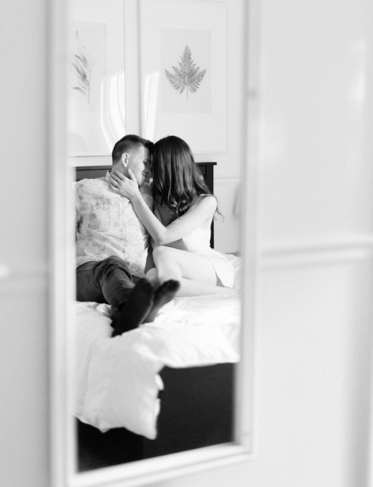 A couple embraces while sitting on their bed in Rochester, Michigan during their at home photos