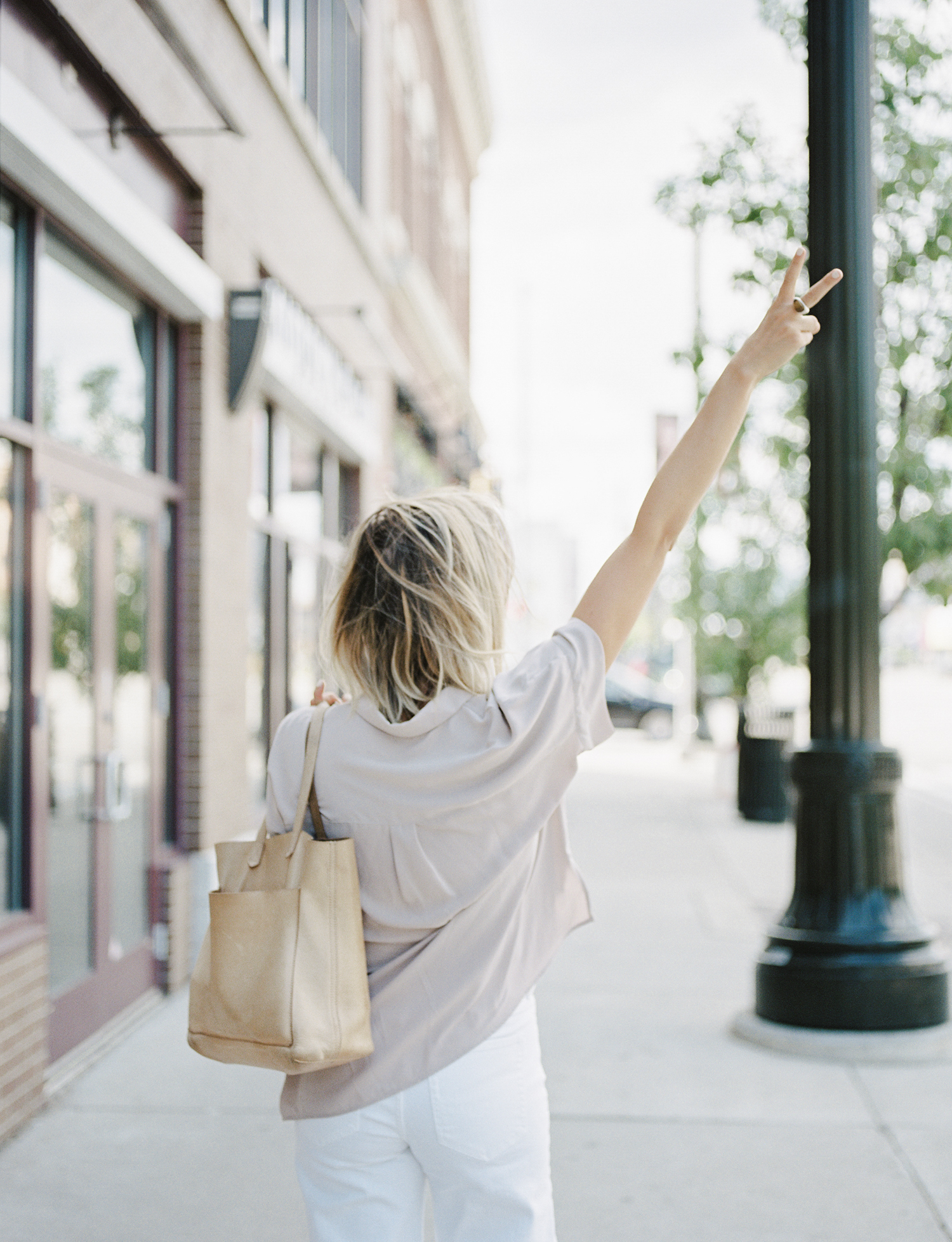 A female creative entrepreneur and designer holds up a peace sign while walking down Woodward ave in Detroit with her madewell bag