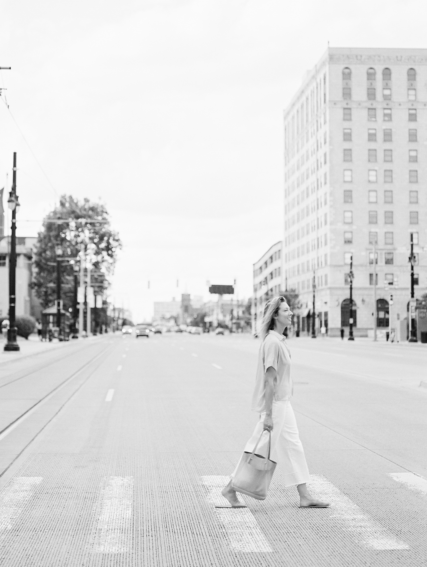 A creative woman business owner walks across Woodward ave near the DIA in Detroit, Michigan