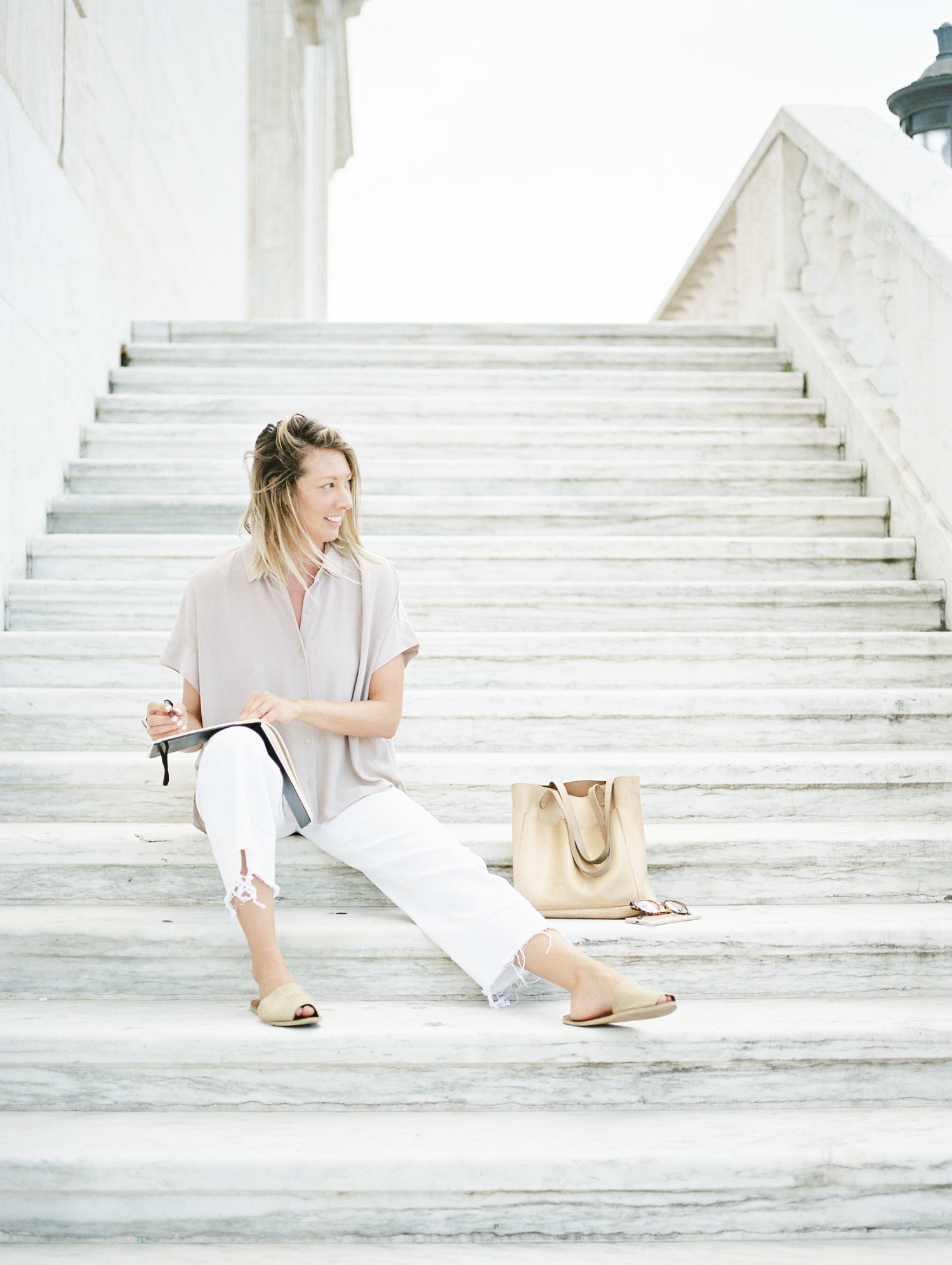 A creative female entrepreneur and designer sits on the steps of the Art Institute in Detroit to sketch during her brand photos