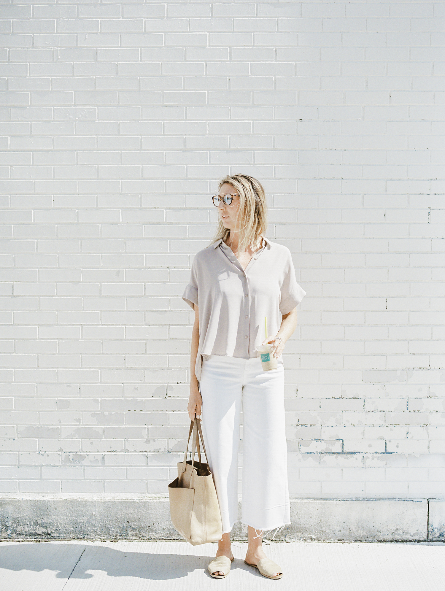 A female designer with New Order Coffee and a Madewell bag pauses in front of a white distressed brick building during her brand photos on film in Detroit, Michigan
