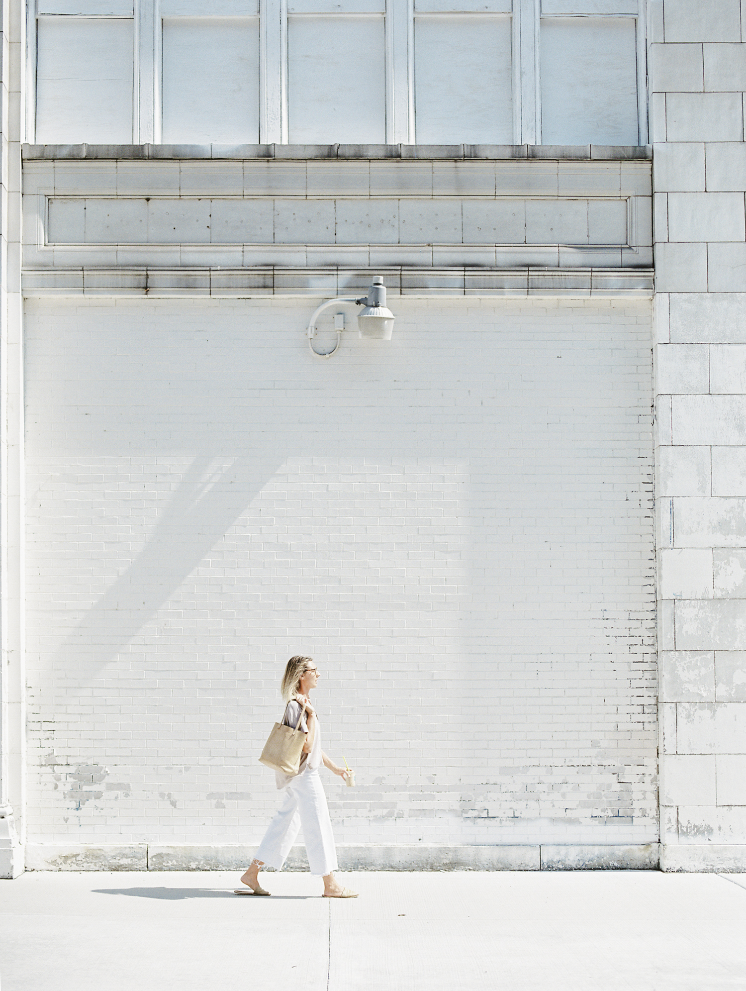 A designer walks along a white distressed brick building in Detroit during her creative brand photo shoot on film
