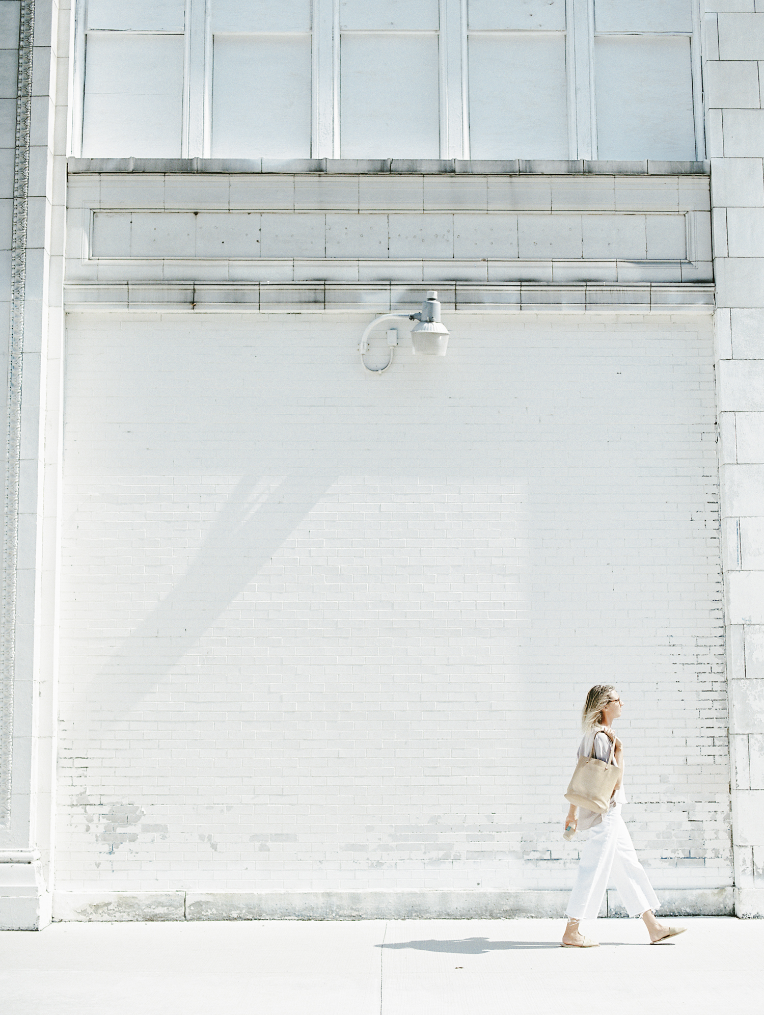 A brand designer walks along a beautiful white distressed brick building in Detroit during her brand photoshoot on film