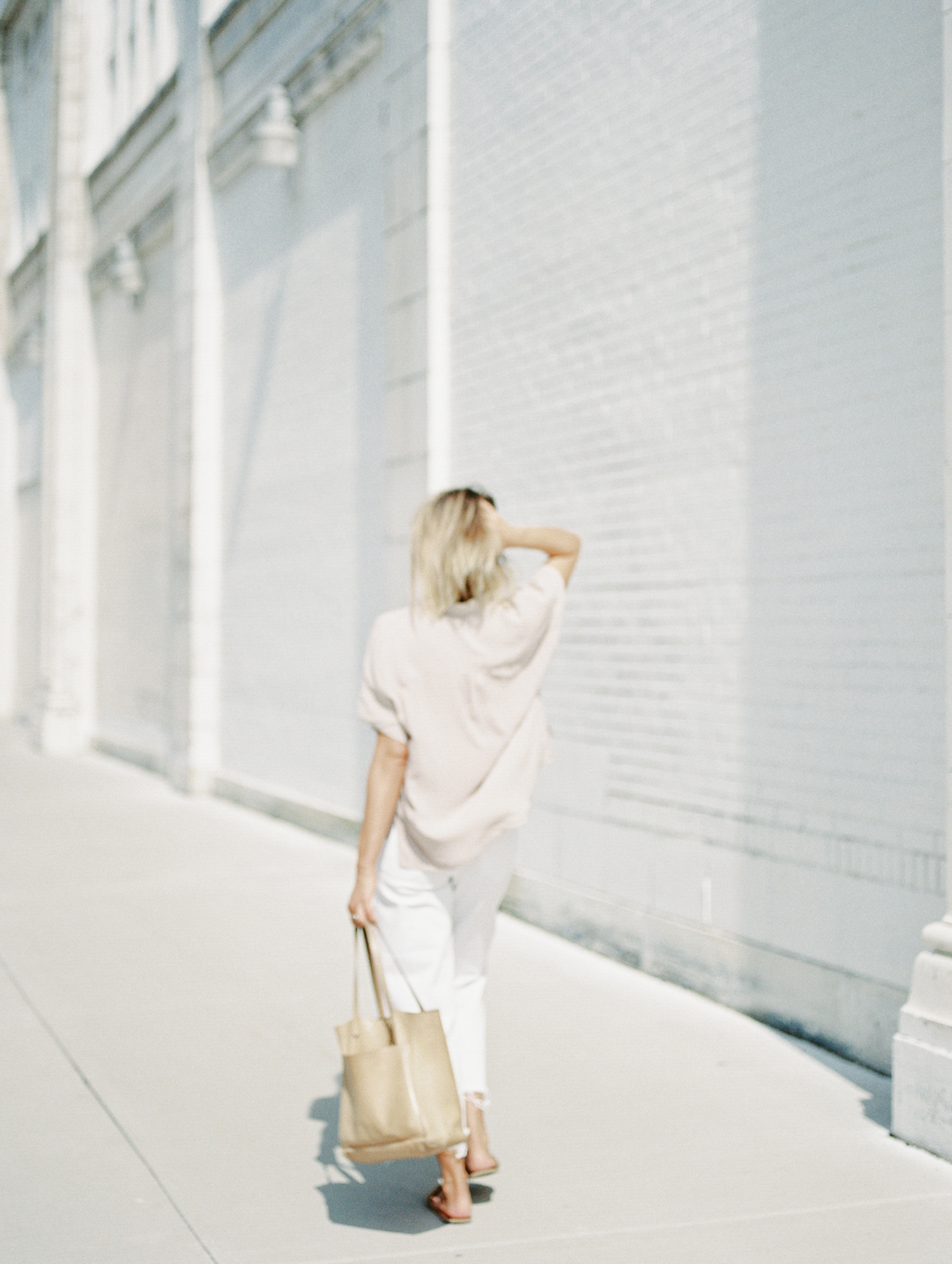 A female entrepreneur and designer casually walks away along a white distressed building in Detroit during her brand photos